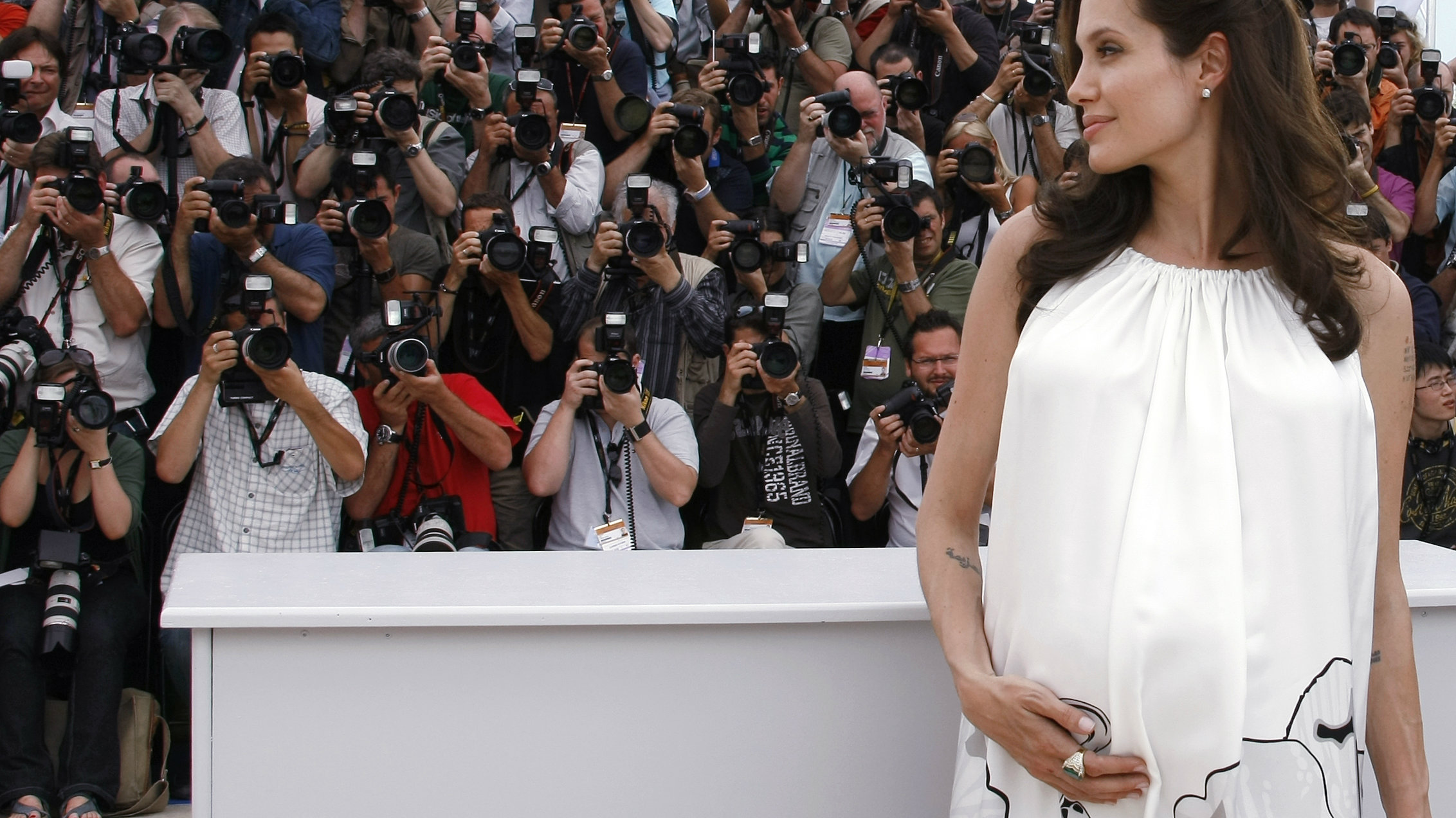 """Voice actor Angelina Jolie places her hand on her stomach during a photocall for the animated film """"Kung Fu Panda"""" by directors Mark Osborne and John Stevenson at the 61st Cannes Film Festival May 15, 2008. REUTERS/Eric Gaillard (FRANCE)"""