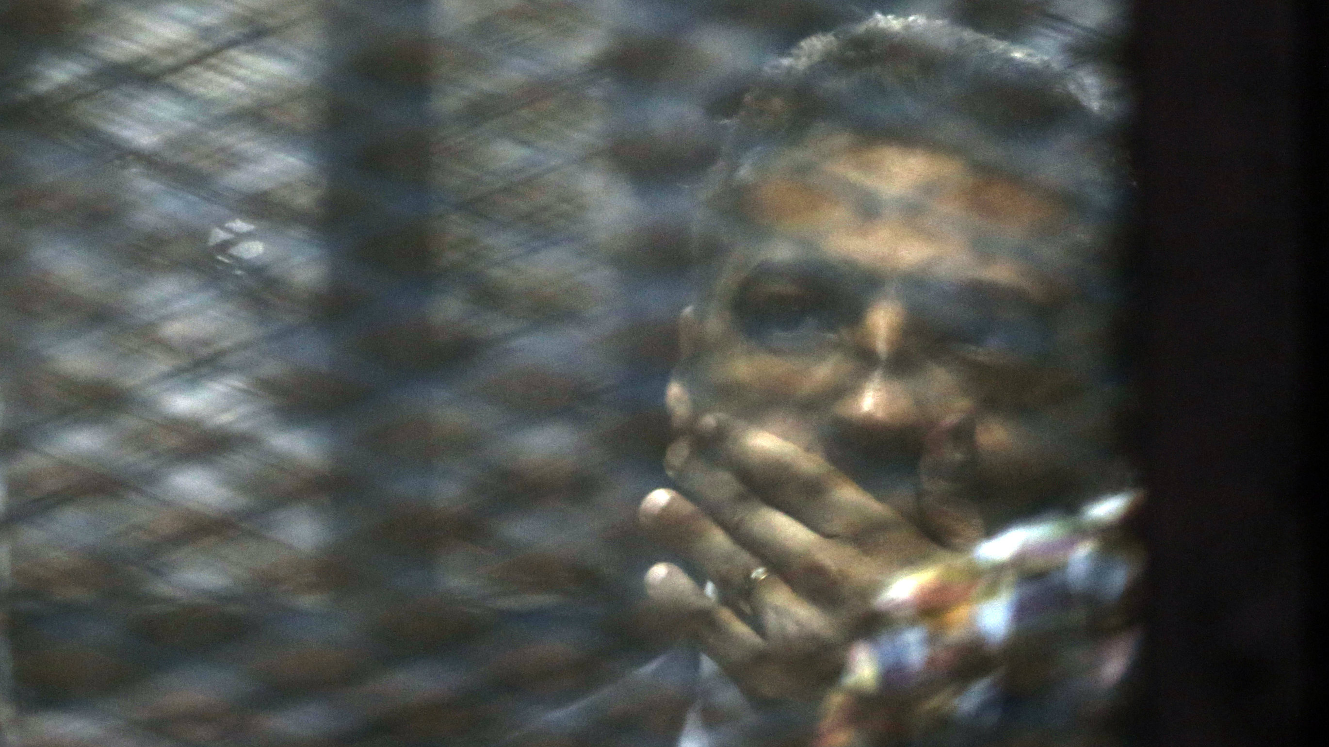 Canadian Al-Jazeera English journalist Mohammed Fahmy, listens to his verdict in a soundproof glass cage inside a makeshift courtroom in Tora prison in Cairo, Egypt, Saturday, Aug. 29, 2015.