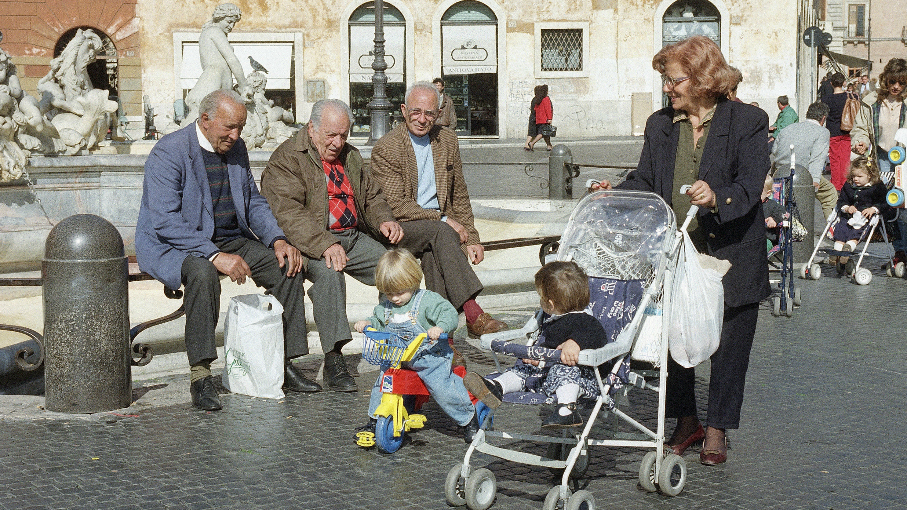 """A grandmother takes several """" baminos"""" for a stroll in Rome's fashionable piazza Navona on oct. 27, 1993. As the Italian government provides little in the way of child care, working parents often must rely on grandparents to tend the kids. The difficulties and expense of raising children may account for Italy's low birth rate, according to sociologists. (AP PhotoGiulio Broglio)"""