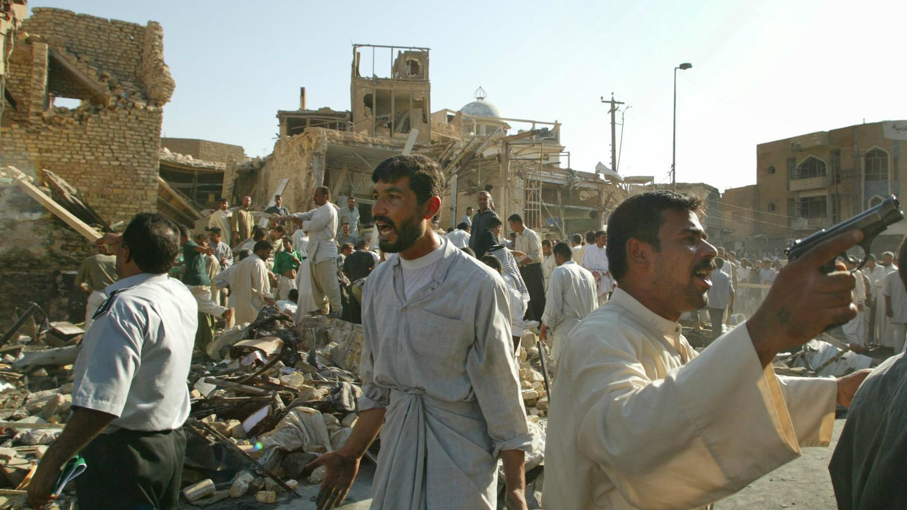 Iraqis try to keep back family members of the dead and injured and other onlookers as people dig through the rubble left after a car bomb exploded next to Imam Ali shrine in Najaf, Iraq killing at least 75 and wounding 150 others Friday August 29, 2003. The car bomb killed Ayatollah Mohammed Baqir al-Hakim, one of the most respected Shiite Muslim clerics in Iraq. (AP Photo/David Guttenfelder)