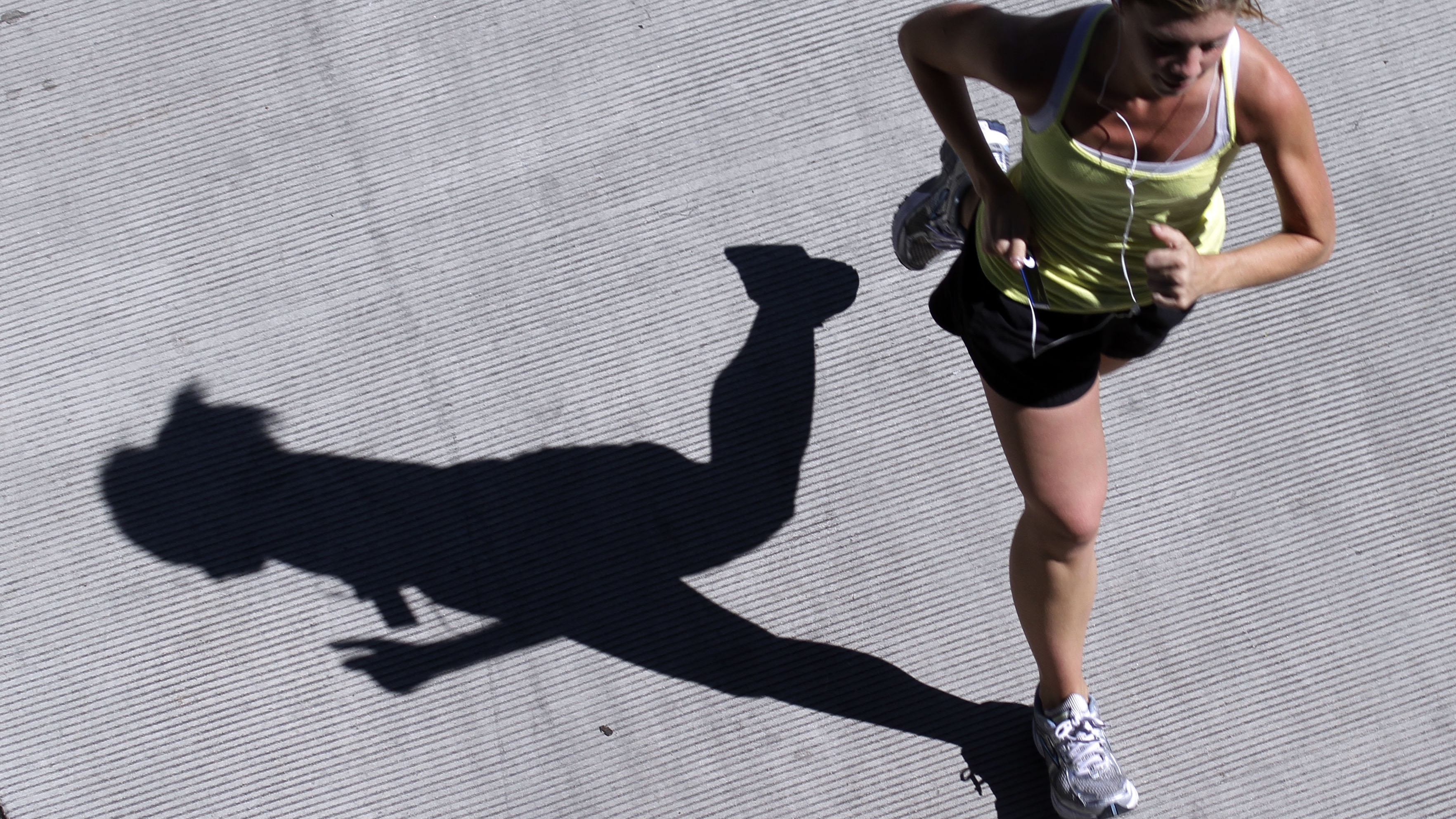A lone jogger casts a long shadow while running at the Tom McCall Waterfront Park in Portland, Ore., Monday, Aug. 1, 2011.