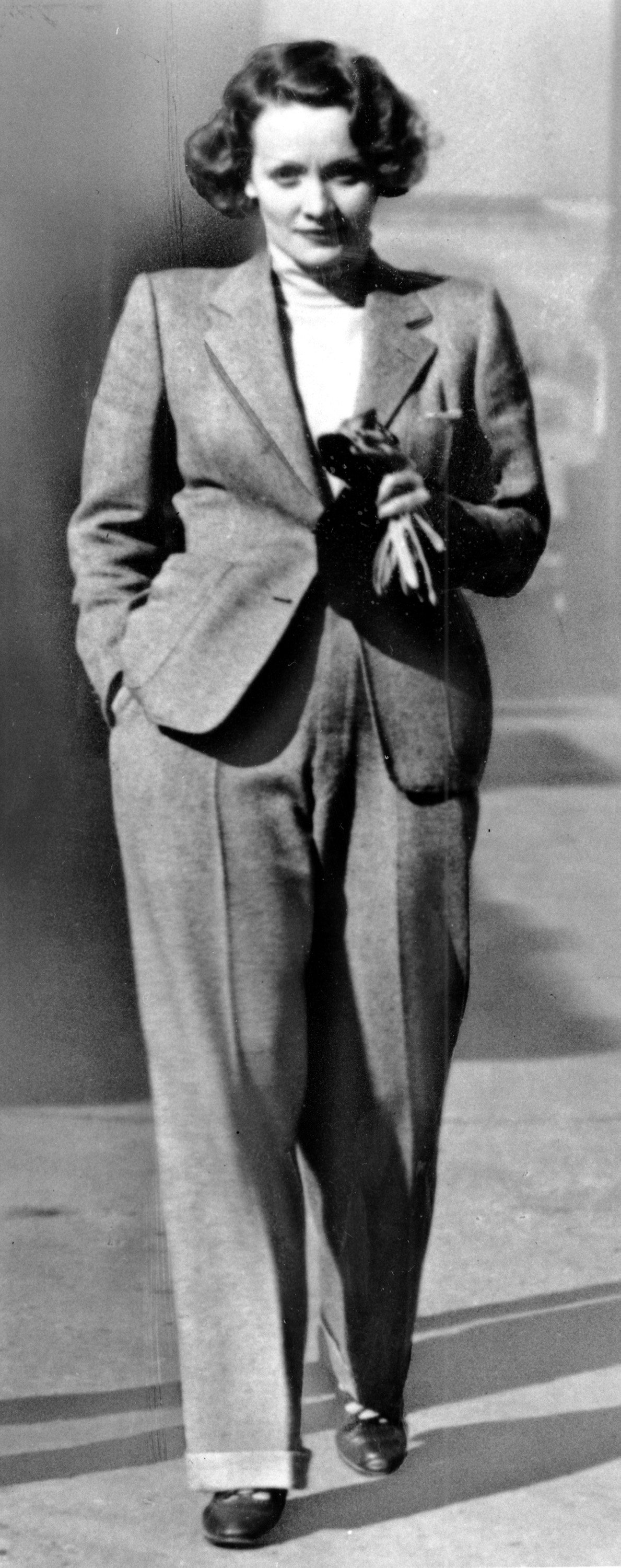 Actress Marlene Dietrich wears a trendsetting masculine style pant suit created by French couturiere Coco Chanel in 1933 at an unknown location.