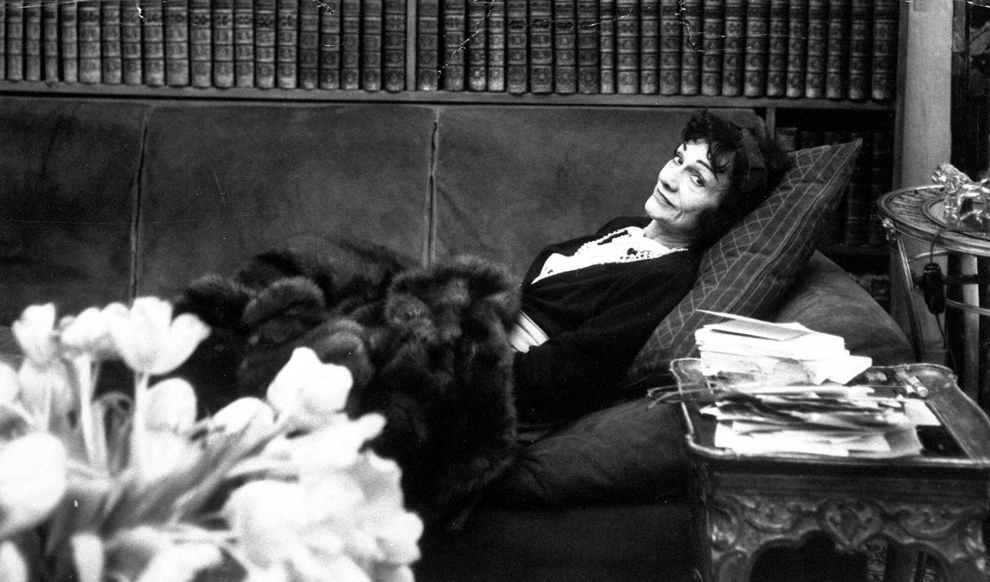 """Gabrielle """"Coco"""" Chanel, back in the fashion world after a lapse of 15 years, relaxes in her book-lined studio above her Paris salon April 21,1954."""