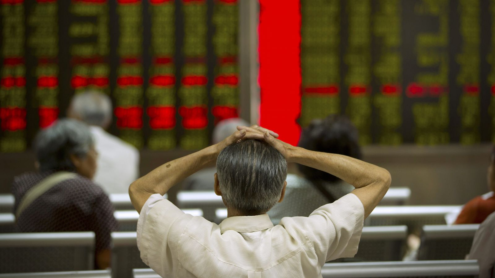 A Chinese investor monitors displays of stock information at a brokerage house in Beijing, Tuesday, July 28, 2015. Shanghai stocks were volatile Tuesday after falling the most in eight years the day before while other Asian markets also flitted between gains and losses. (AP Photo/Mark Schiefelbein)