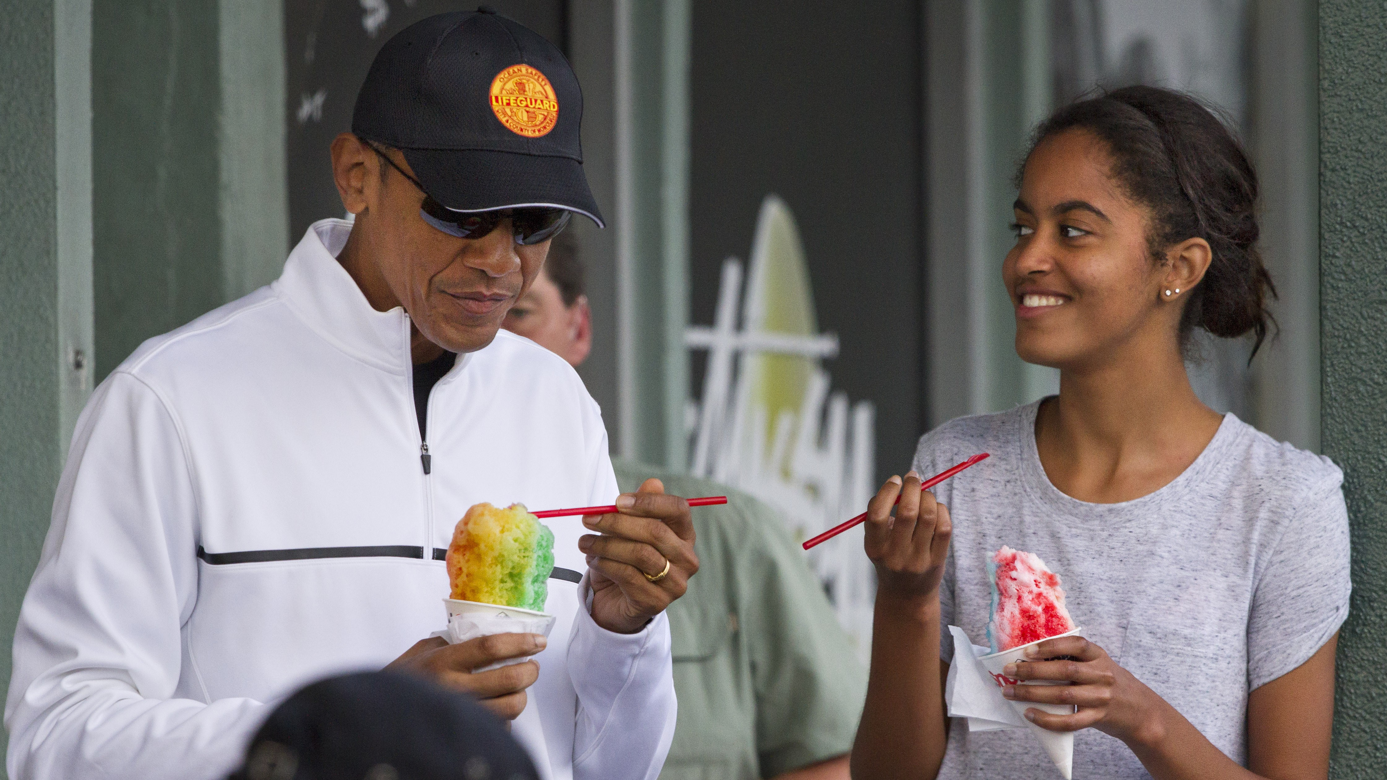 President Barack Obama eats shave ice with daughter Malia Obama at Island Snow, Thursday, Jan. 1, 2015, in Kailua, in Hawaii during the Obama family vacation.