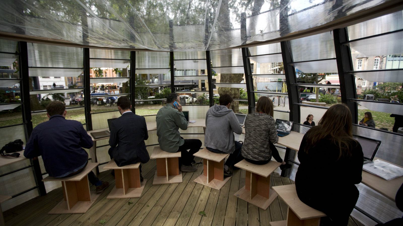 People pose for the media and work during an event to launch TREExOFFICE in Hoxton Square, London. Built around a tree, the concept in co-working space has eight workstations available to be hired. (AP Photo/Matt Dunham)