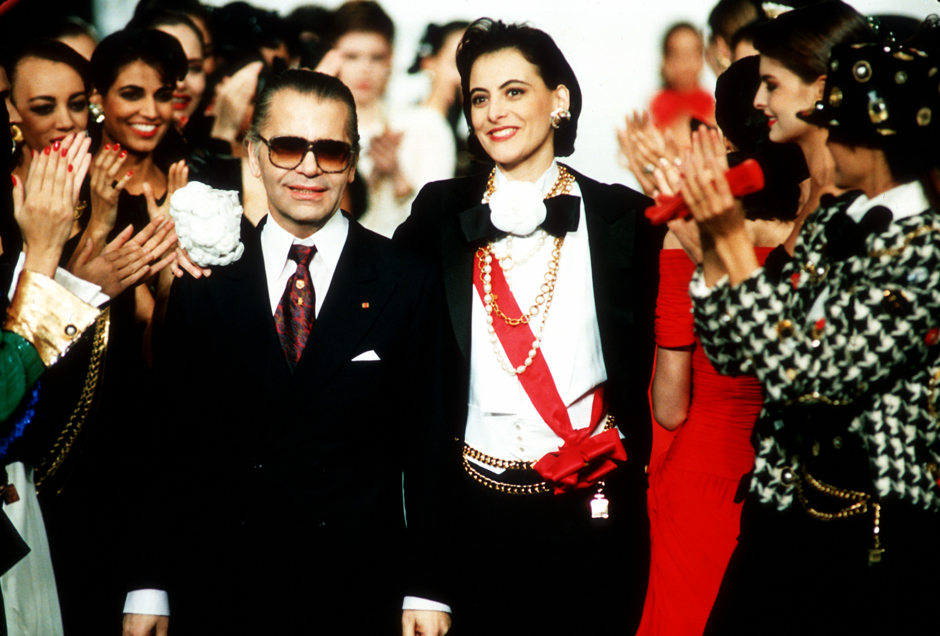 Chanel's top model Ines de la Fressange has her arm around West German designer Karl Lagerfeld as models applaud at the end of Chanel's fall and winter 1987 ready-to-wear collection in Paris, France, March 23, 1987.