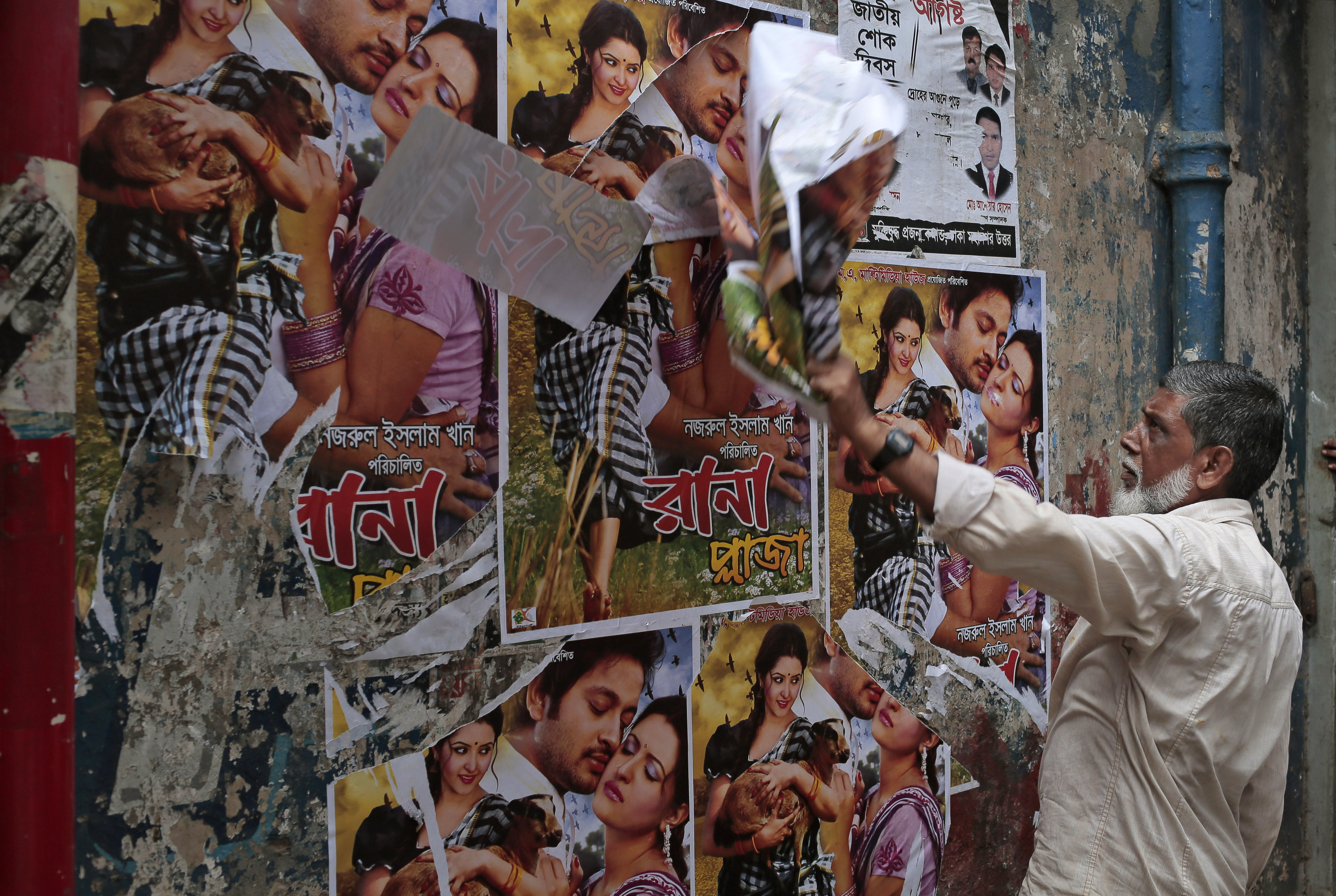 "A Bangladeshi movie theatre worker removes posters of a film ""Rana Plaza"" in Dhaka, Bangladesh, Tuesday, Aug. 25, 2015. Bangladesh's High Court has imposed a six-month ban on the screening of the movie about a garment worker who was rescued from the rubble 17 days after a five-story factory complex collapsed more than two years ago, killing more than 1,000 people."