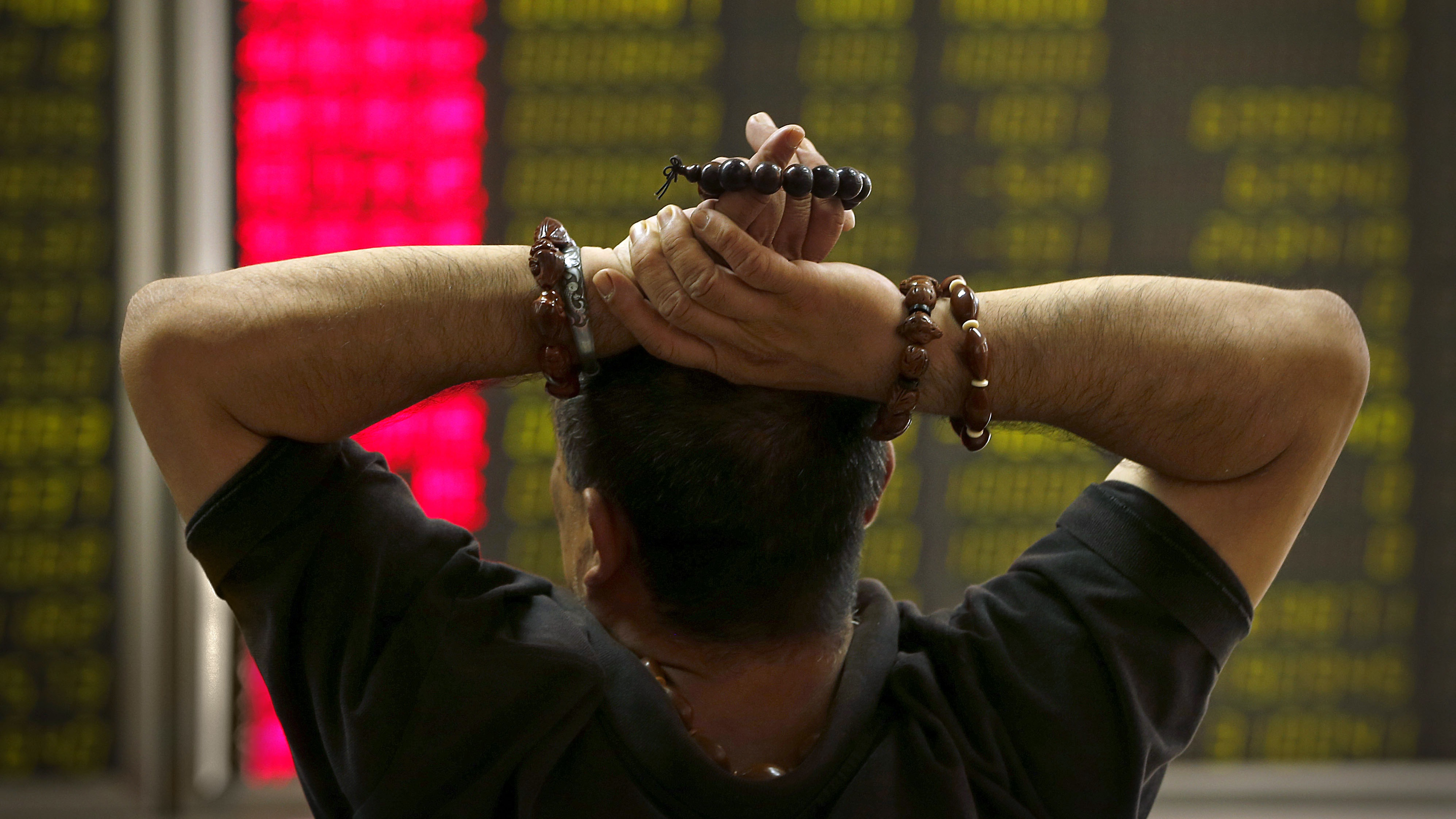A Chinese investor monitors stock prices at a brokerage house in Beijing, Monday, Aug. 24, 2015. Stocks tumbled across Asia on Monday as investors shaken by the sell-off last week on Wall Street unloaded shares in practically every sector.