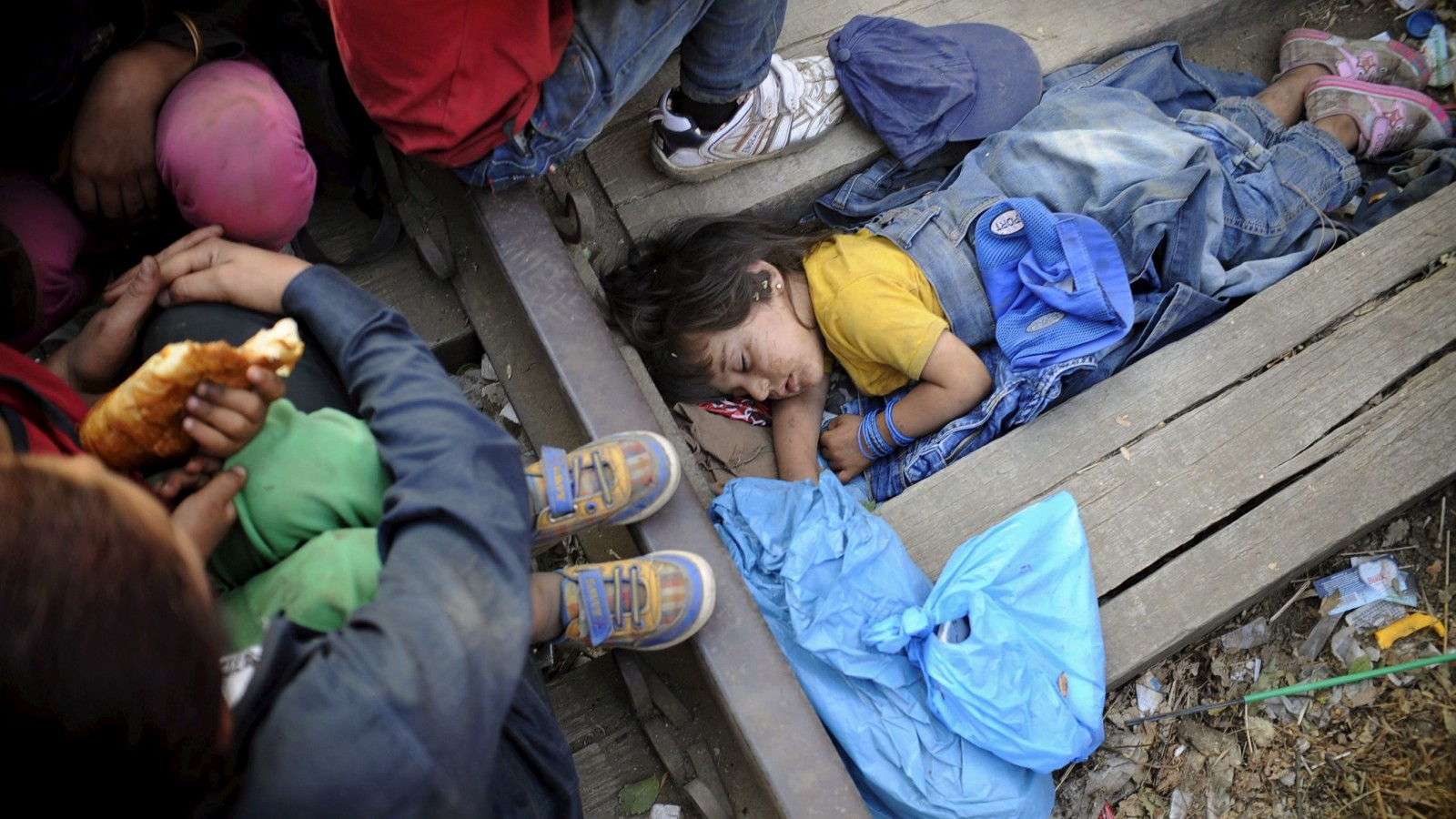 Four-year-old Rashida from Kobani, Syria, part of a new group of more than a thousand immigrants, sleeps as they wait at border line of Macedonia and Greece to enter into Macedonia near Gevgelija railway station August 20, 2015. Thousands of migrants kept up the wait on in a small Macedonian town in the hope of travelling onwards to Western Europe. After days of crowds overwhelming the small station at Gevgelija, Macedonian authorities have established special trains for migrants from south to the northern border with Serbia. REUTERS/Ognen Teofilovski  - RTX1OVRO