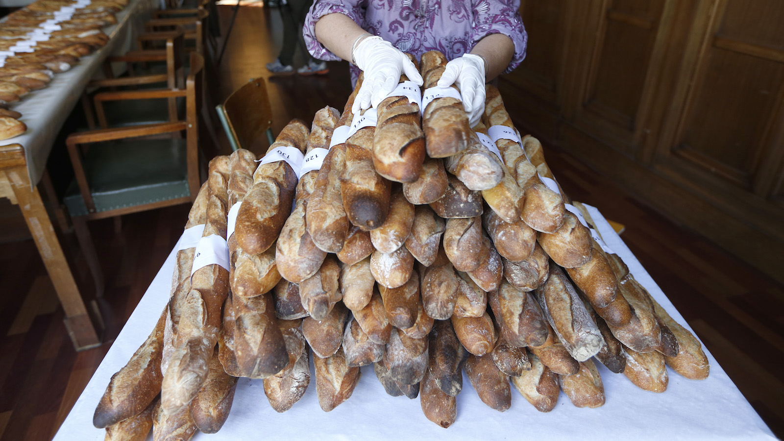 An assistant stacks baguettes which are not selected in the competition for the Best Baguette of Paris 2013 annual prize in Paris