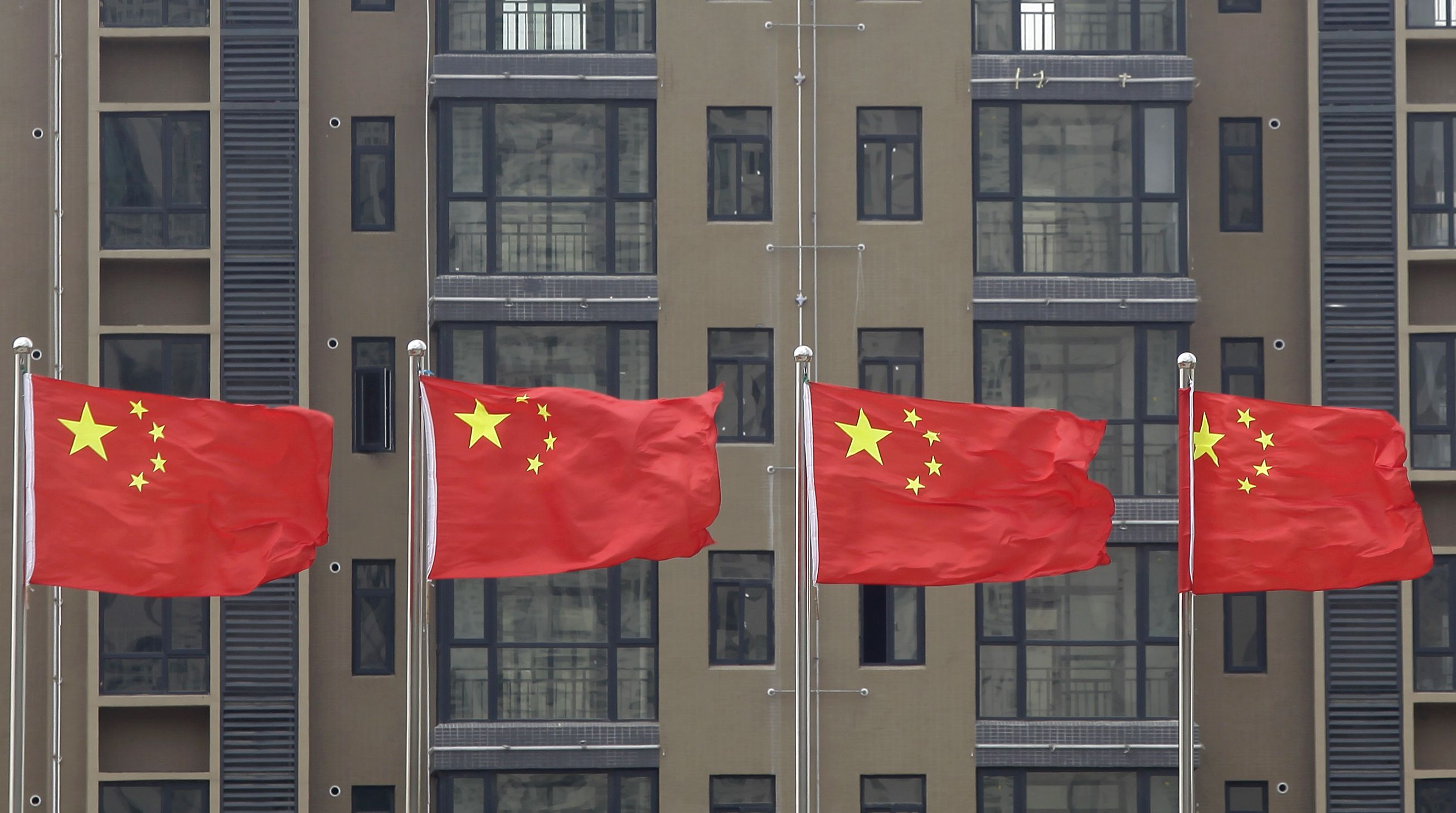 DATE IMPORTED:July 10, 2012Chinese national flags fly in front of a newly-built residential apartment in Wuhan, Hubei province July 10, 2012. China must firmly maintain its property tightening measures to cool housing prices, Premier Wen Jiabao was quoted as saying on Saturday, underscoring official concerns about renewed bubbles as the central bank ratchets up policy easing to support growth. REUTERS/Stringer