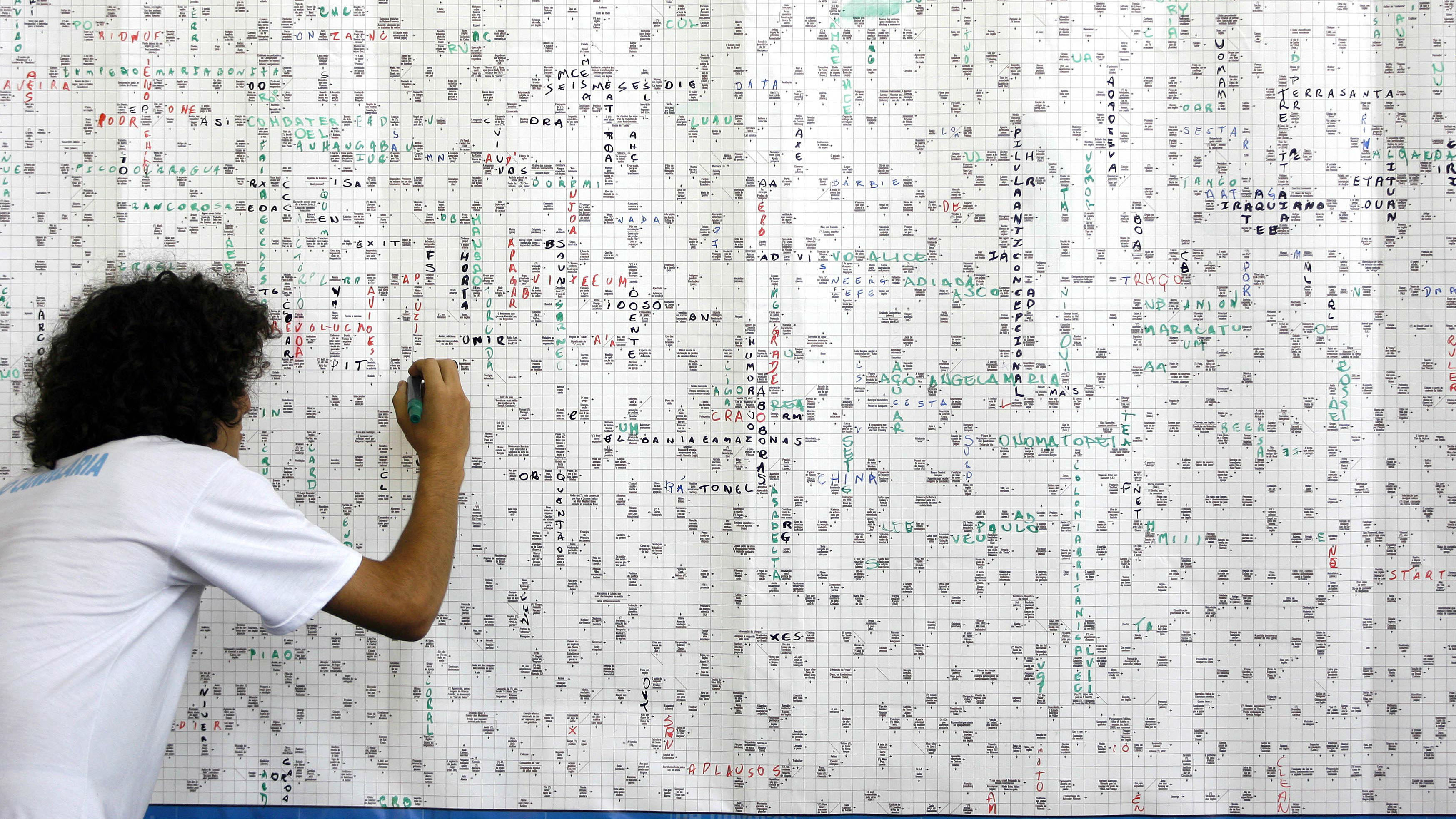 A visitor writes in a giant crossword displayed during Sao Paulo's Book Biennal, on Thursday, March 9, 2006. The crossword is 3.25 meters wide (10.66 feet) and 1.5 meters in height (4.92 feet) and contains 3,200 quizes. The creators, Ediouro publishing, will present it to the Guinness organization to be considered as the world's largest crossword puzzle.