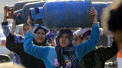 Women carry gas cylinders to fill them at a distribution point in Cairo January 19, 2015.