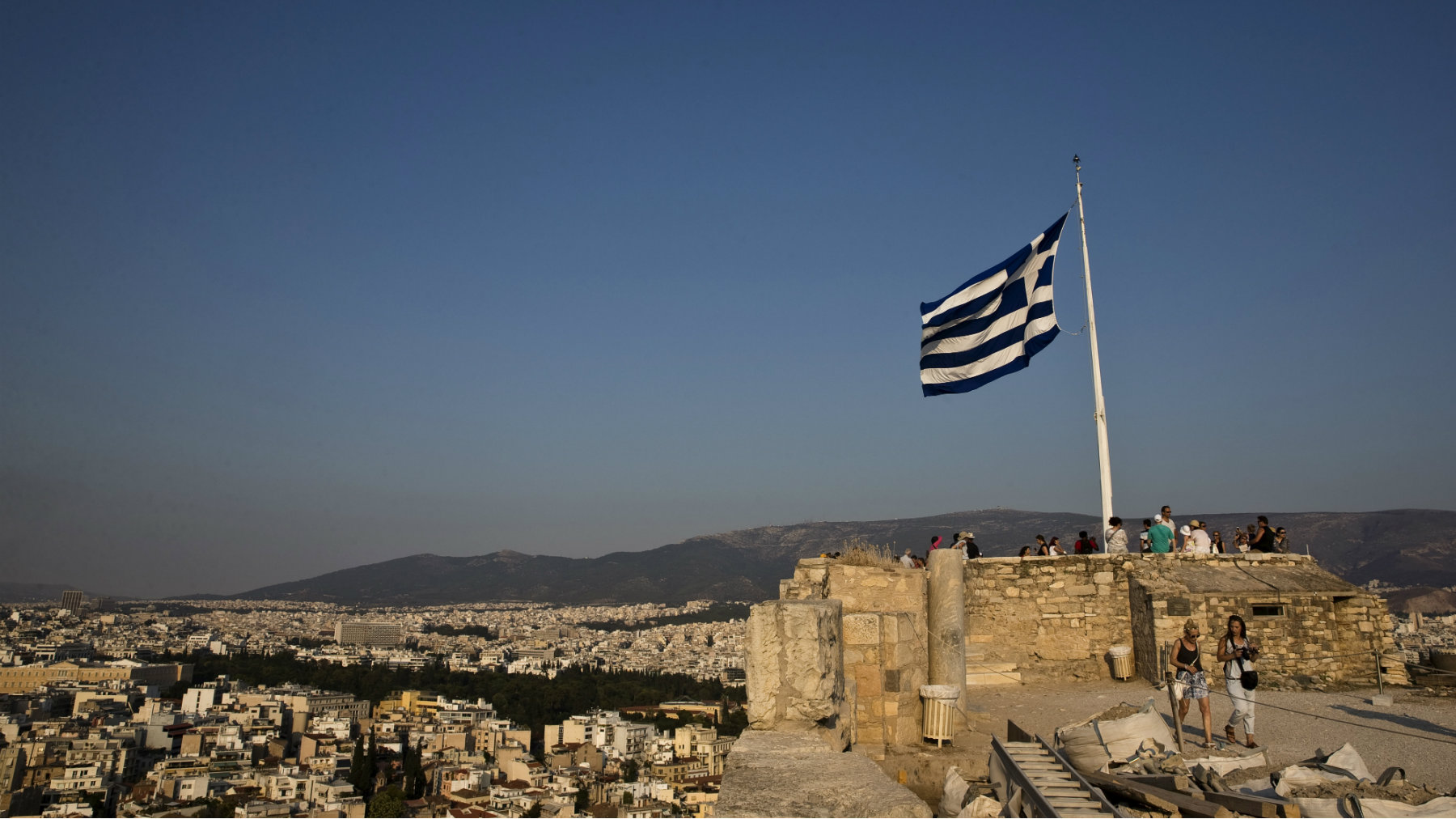 A Greek flag flutters in the wind as tourists visit the archaeological site of the Acropolis hill in Athens.