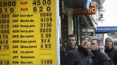 A man looks at an information panel showing the exchange rate, in Kiev, Ukraine.