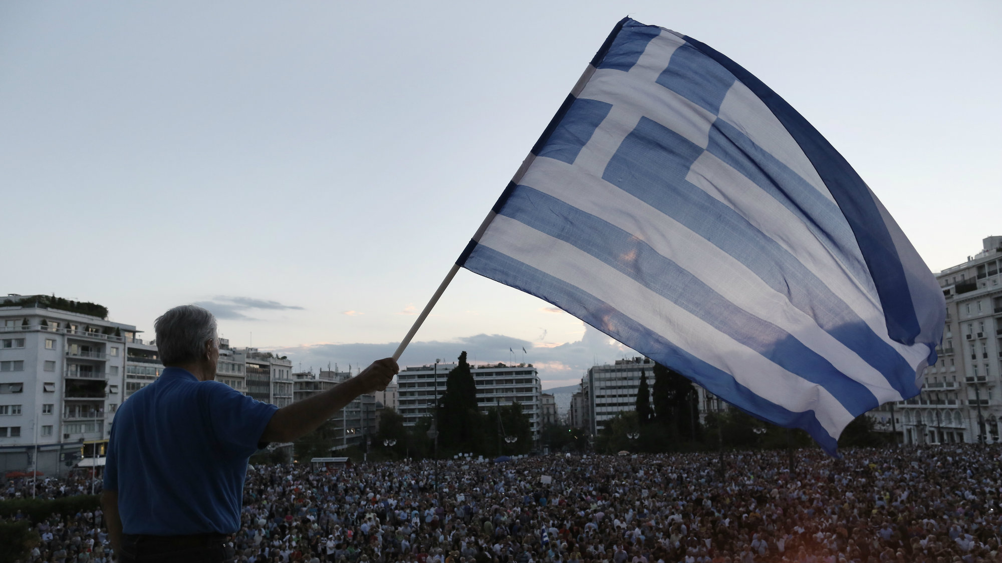 A demonstrator waves a Greek flag as he stands on the parliament demanding that Greece remains in the Eurozone, outside the parliament in Athens, Greece, 18 June 2015.