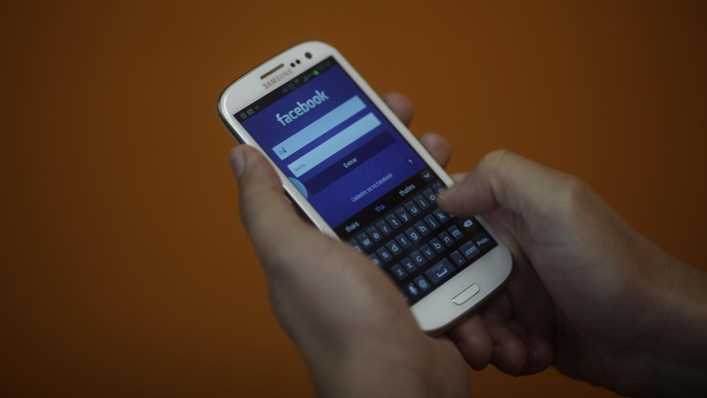 A smartphone user logs into his Facebook account in Rio de Janeiro