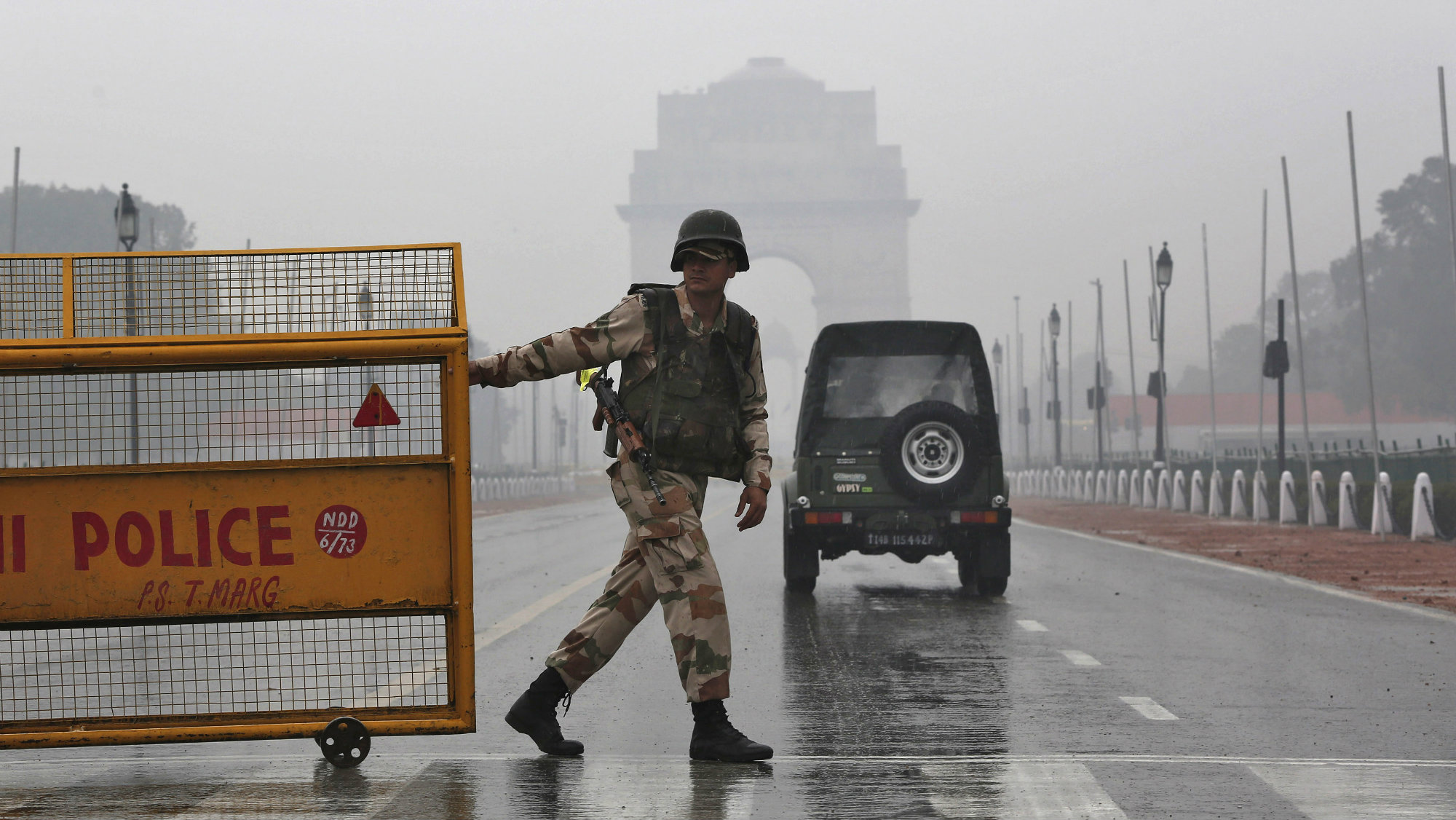 An Indian security personnel pulls a barricade to block the road in front of India Gate as it rains in New Delhi January 22, 2015. India's capital will turn into a virtual fortress for U.S. President Barack Obama's visit this weekend, with heightened security measures, including an extended no-fly zone, to protect the world's most powerful leader. REUTERS/Adnan Abidi (INDIA - Tags: MILITARY ANNIVERSARY POLITICS)
