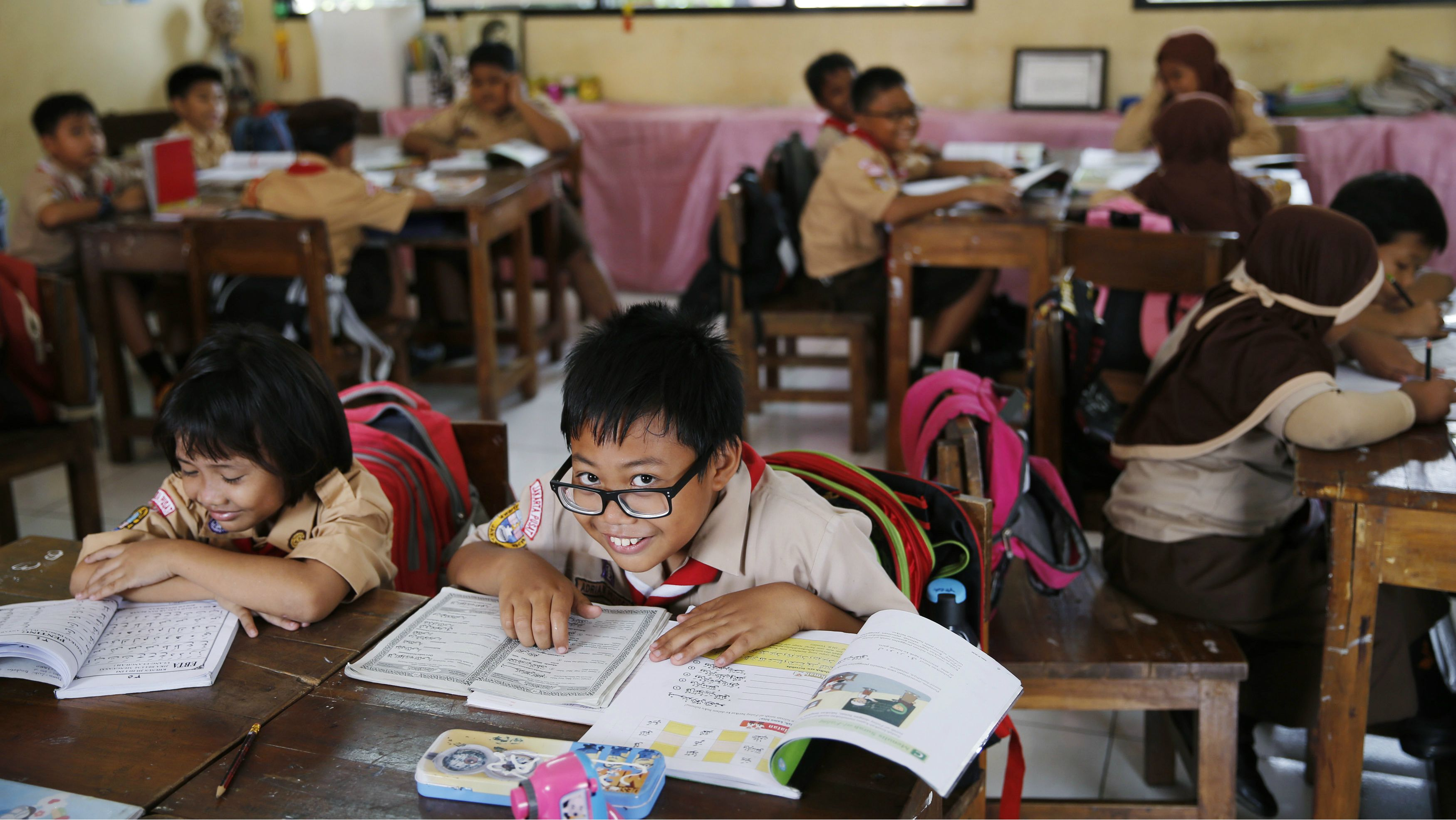 A student reacts to the camera as a teacher teaches the 2013 curriculum inside a classroom at Cempaka Putih district in Jakarta, October 15, 2014.