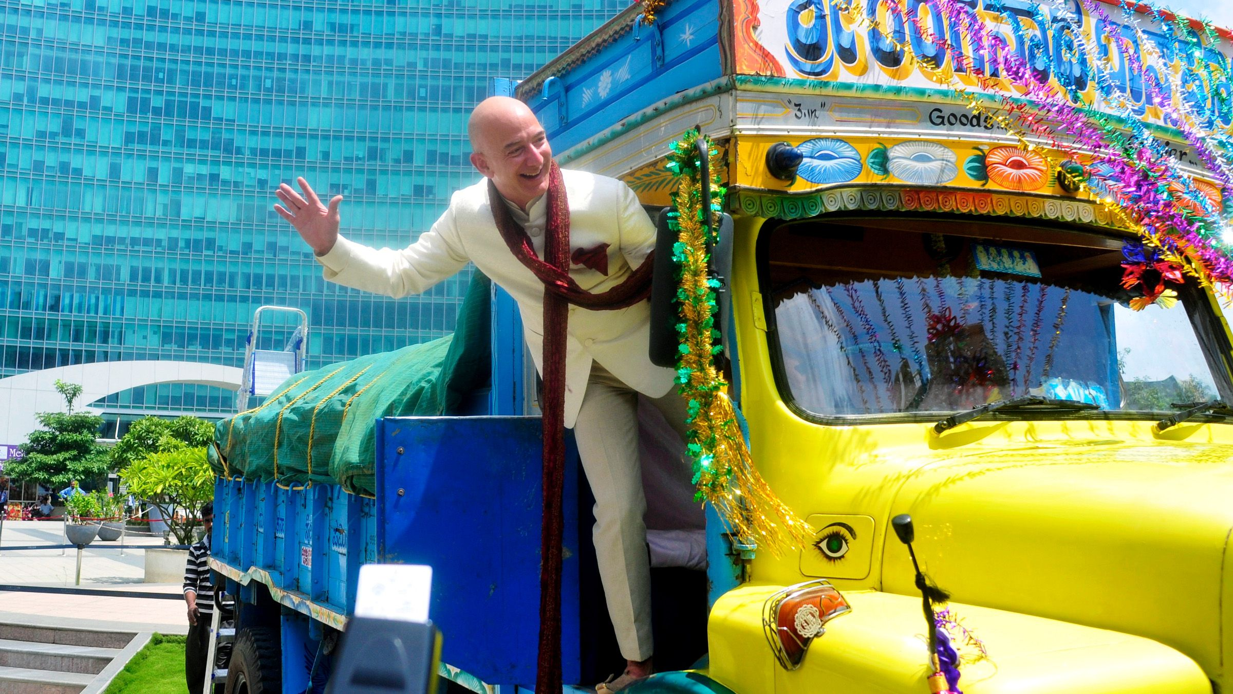 Jeff Bezos, founder and CEO of Amazon, poses as he stands on a supply truck during a photo opportunity at the premises of a shopping mall in the southern Indian city of Bangalore September 28, 2014.