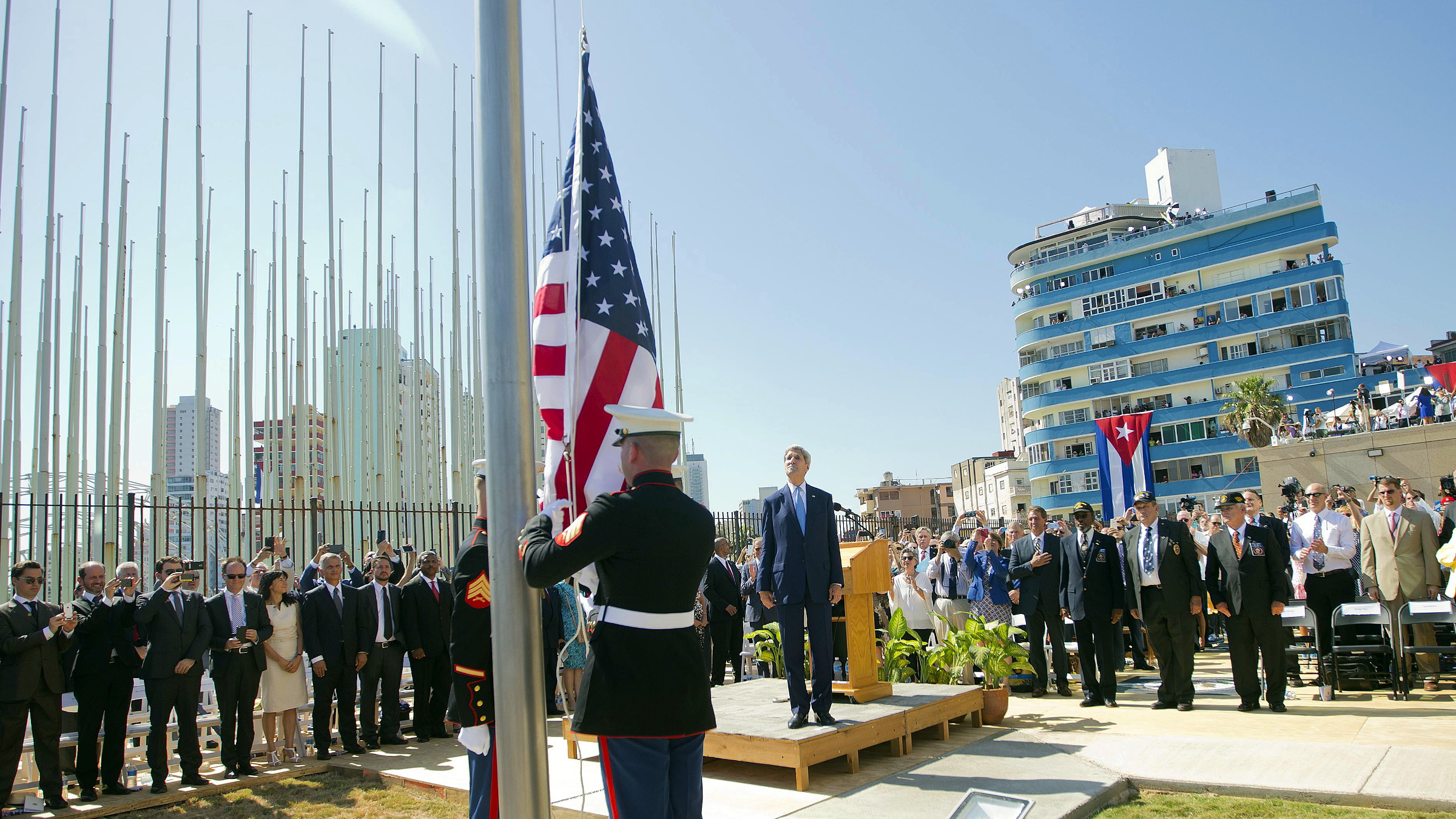 U.S. Secretary of State John Kerry (C) stands with other dignitaries as members of the U.S. Marines raise the U.S. flag over the newly reopened embassy in Havana, Cuba, August 14, 2015. Watched over by Kerry, U.S. Marines raised the American flag at the embassy in Cuba for the first time in 54 years on Friday, symbolically ushering in an era of renewed diplomatic relations between the two Cold War-era foes.