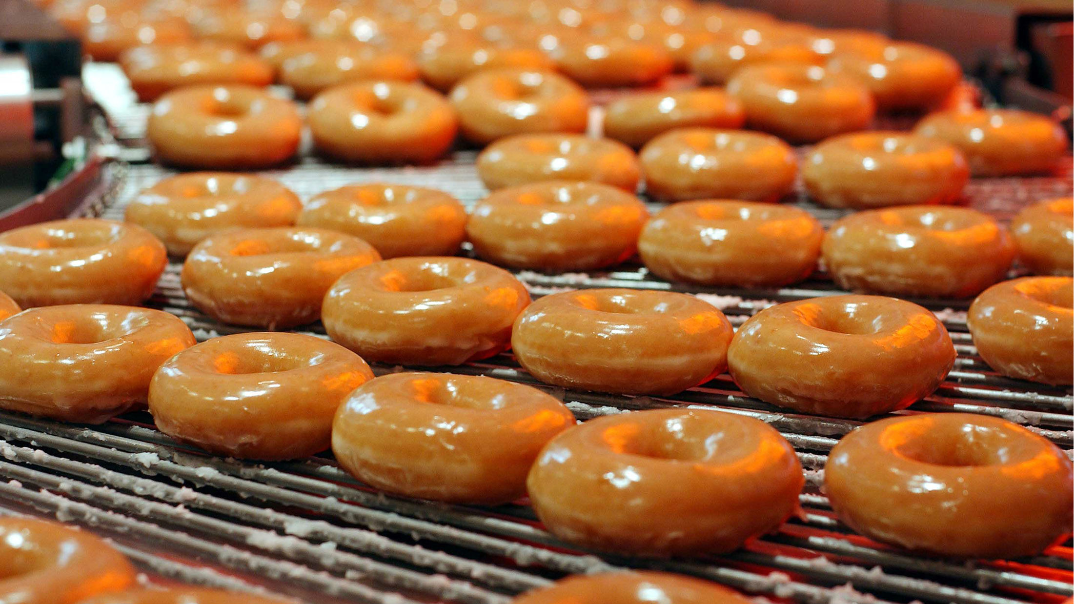 Krispy Kreme doughnuts go into production at the opening of the store at Harrods in London, October, 3, 2003. The U.S. chain opened its first European outlet in London on Friday.