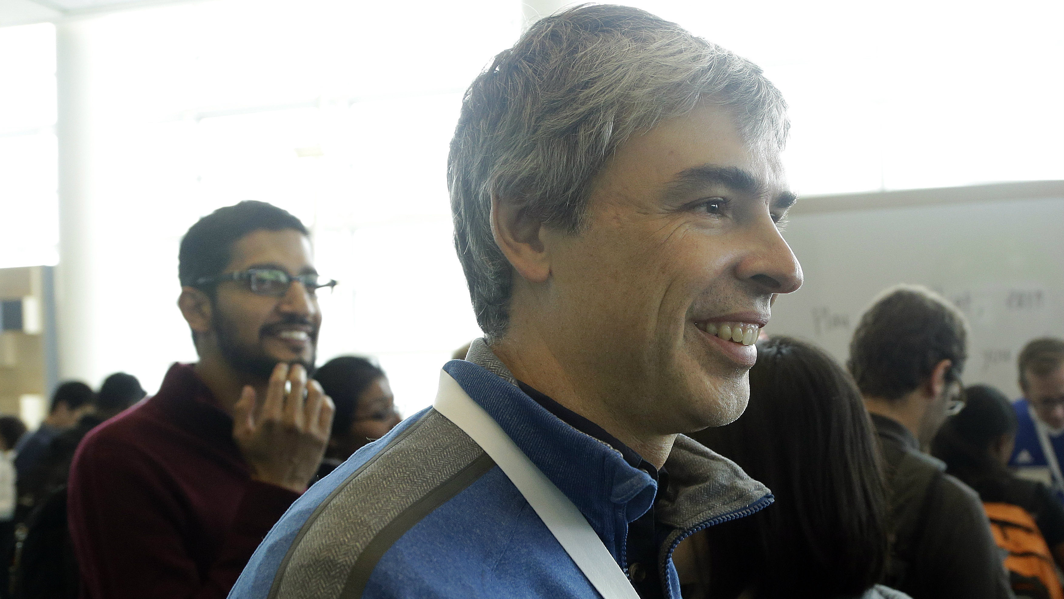 Google CEO Larry Page, foreground, and Sundar Pichai, senior vice president of Android, Chrome and Apps, left, walk along the demo floor at Google I/O 2014 in San Francisco, Wednesday, June 25, 2014. As the Internet giant's Android operating system stretches into cars, homes and smartwatches, this year's annual confab will expand on its usual focus on smartphones and tablets. (AP Photo/Jeff Chiu)