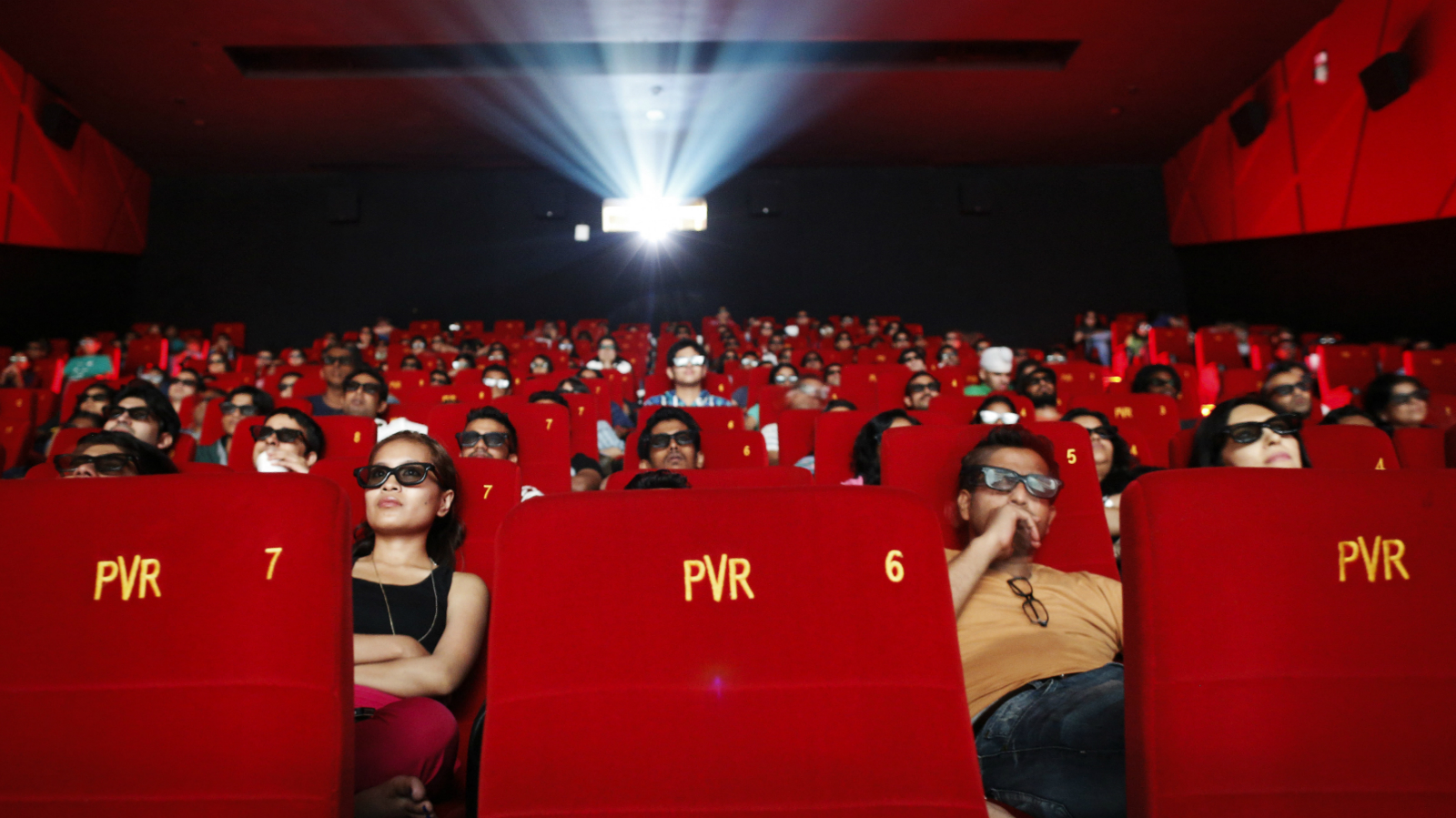 Cinema-goers wearing 3D glasses watch a movie at a PVR Multiplex in Mumbai November 10, 2013. Multiplex operators like PVR Ltd, Inox Leisure, Reliance Mediaworks and Mexican chain Cinepolis are scrambling to set up theatres targeting the rapidly growing number of middle-class Indians willing to pay to watch Bollywood movies in more comfortable surroundings. The potential is huge, provided operators can find the right location in a country where prime urban real estate is costly and in short supply. Picture taken November 10, 2013. To match MULTIPLEX-INDIA/ REUTERS/Danish Siddiqui (INDIA - Tags: SOCIETY BUSINESS ENTERTAINMENT)