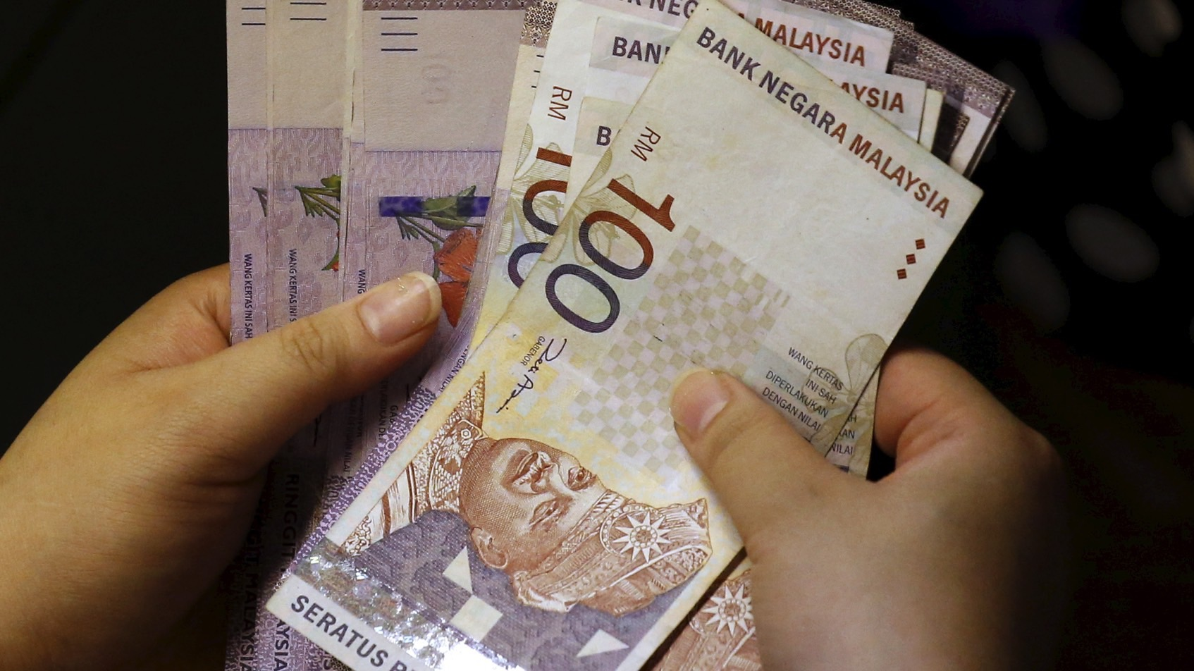 A customer counts her ringgit notes outside a money changer at the central business district in Singapore