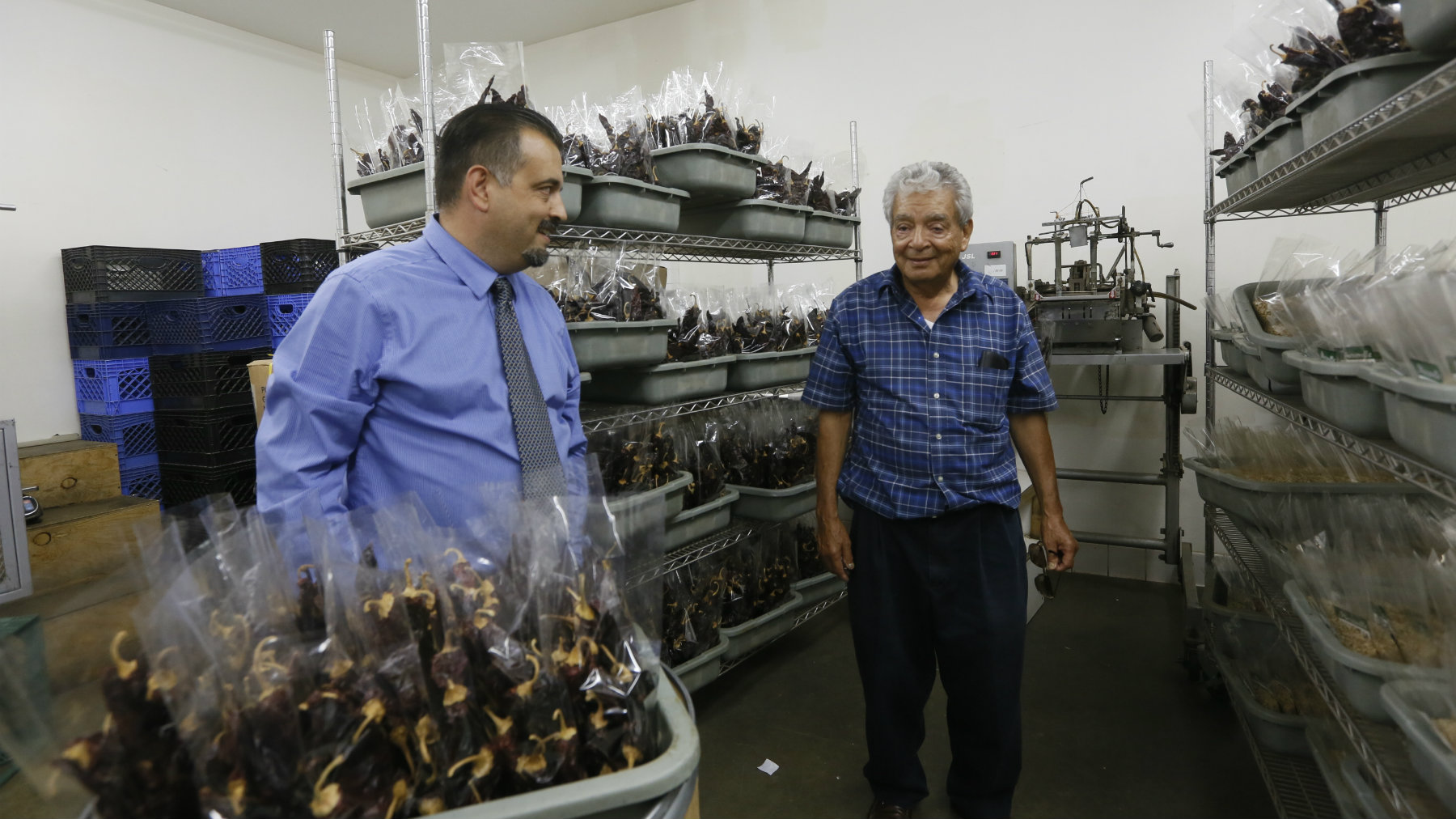 Omar Martinez, left, with his father, Jose Guadalupe pose in 2013 at their family-owned Miravalle Foods spices and herbs business in El Monte, California.