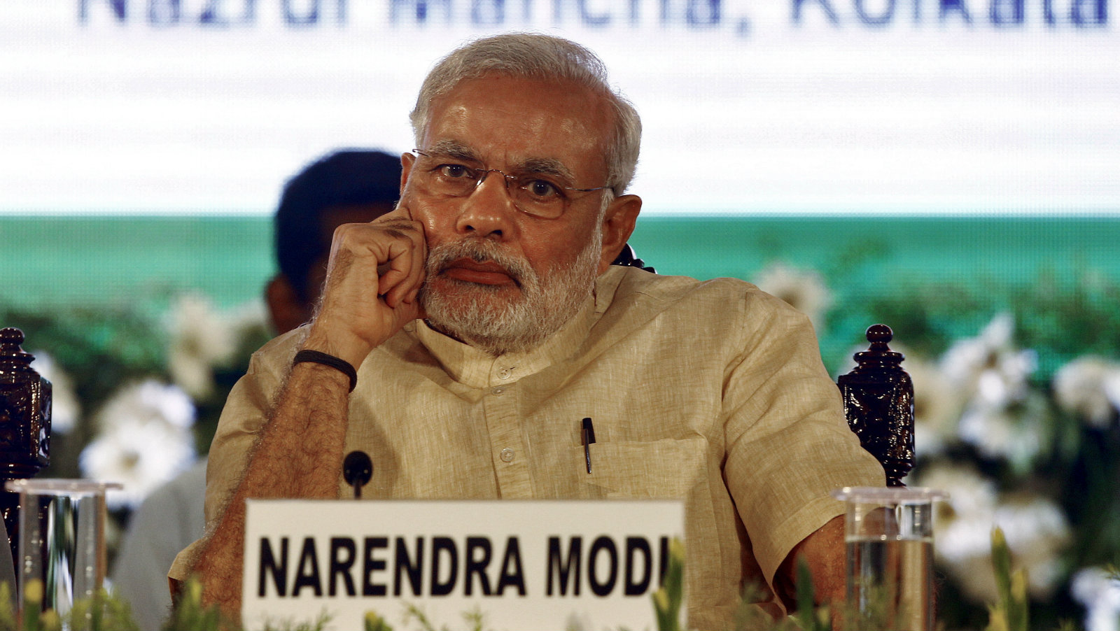 India's Prime Minister Narendra Modi listens to a speaker ahead of launching three new national social security schemes at a function in Kolkata May 9, 2015. Modi on Saturday launched Pradhan Mantri Jeevan Jyoti Bima Yojana (PMJJBY), Pradhan Mantri Suraksha Bima Yojana (PMSBY) and Atal Pension Yojana (APY) during the function, local media reported.