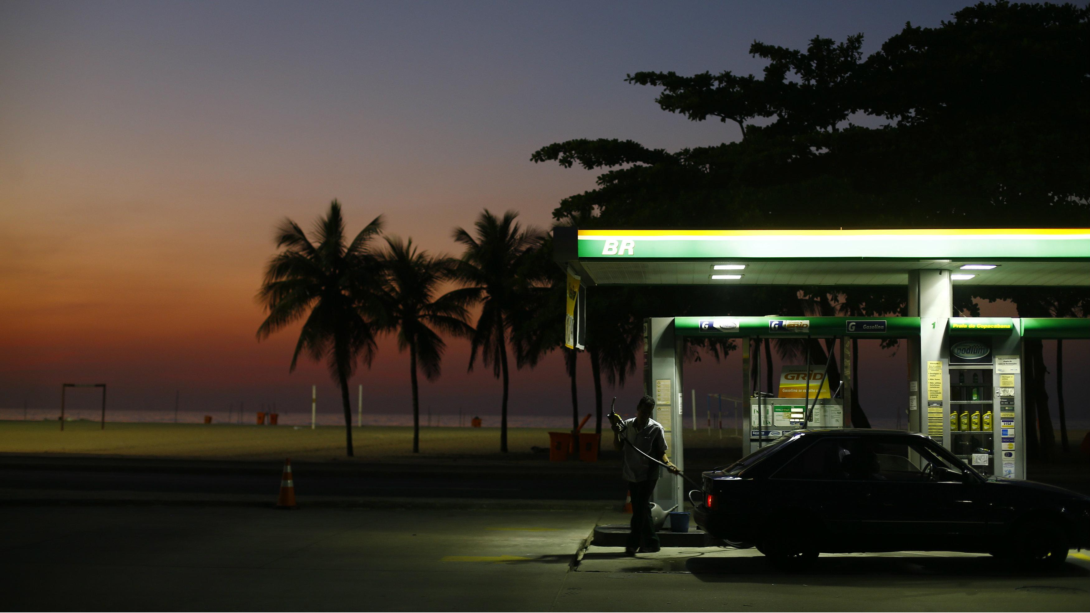 A worker prepares to fill a car at a gas station close to Copacabana beach in Rio de Janeiro, January 12, 2015.