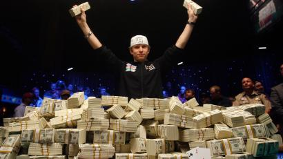 In this Nov. 11, 2008 file photo, Peter Eastgate of Denmark poses with a pile of cash after winning the World Series of Poker championship in Las Vegas. Eastgate won more than $9 million. (AP Photo/Isaac Brekken/FILE)