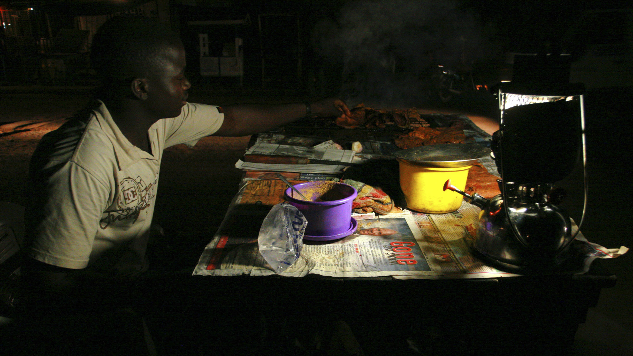 A man prepares roasted meat on a charcoal stove at his stall lit with a paraffin lamp along a street in Lagos September 16, 2007. Thousands of the city's residents have no access to electricity and live in darkness without it. REUTERS/Akintunde Akinleye