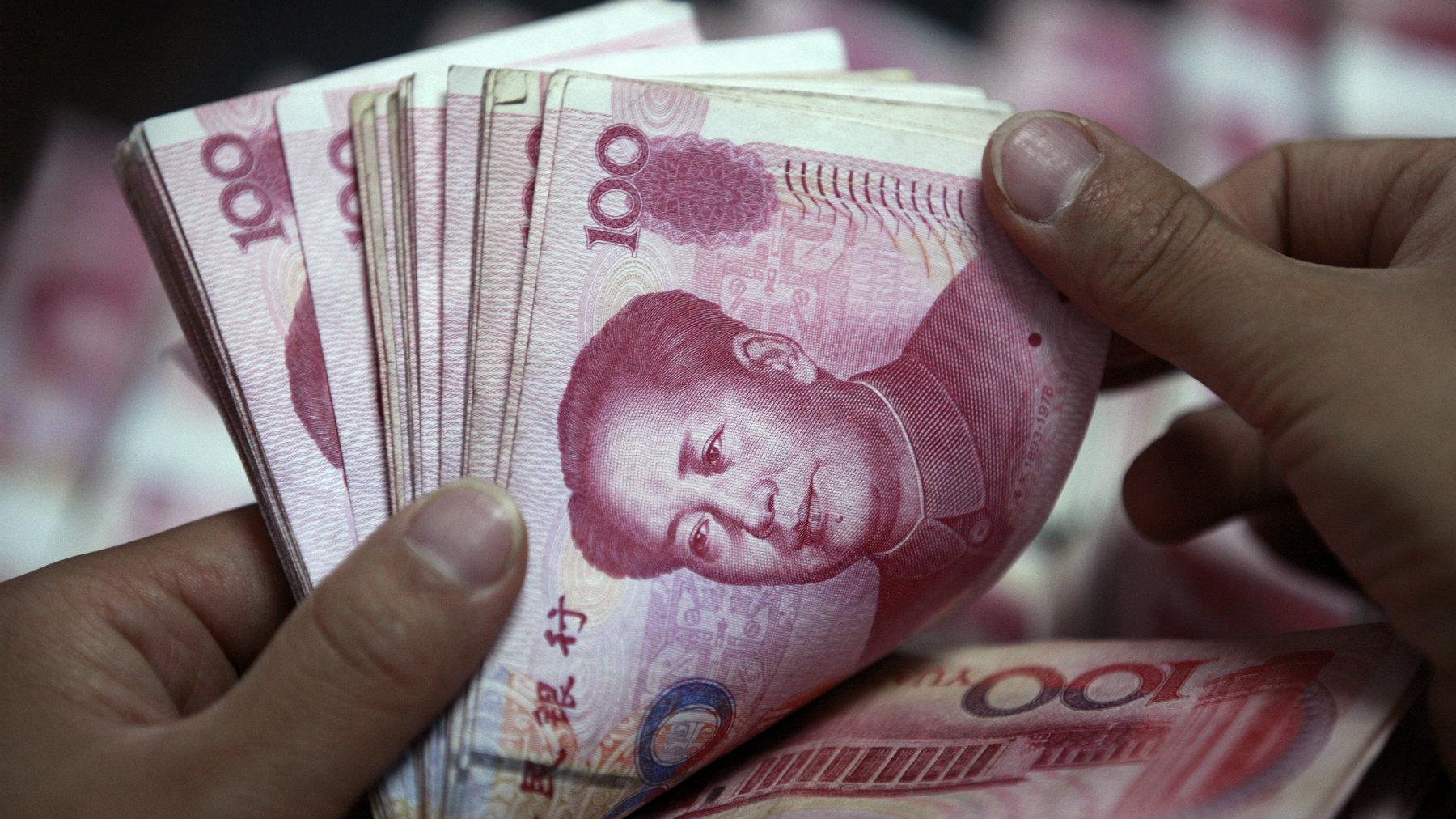A bank clerk counts Chinese yuan banknotes.