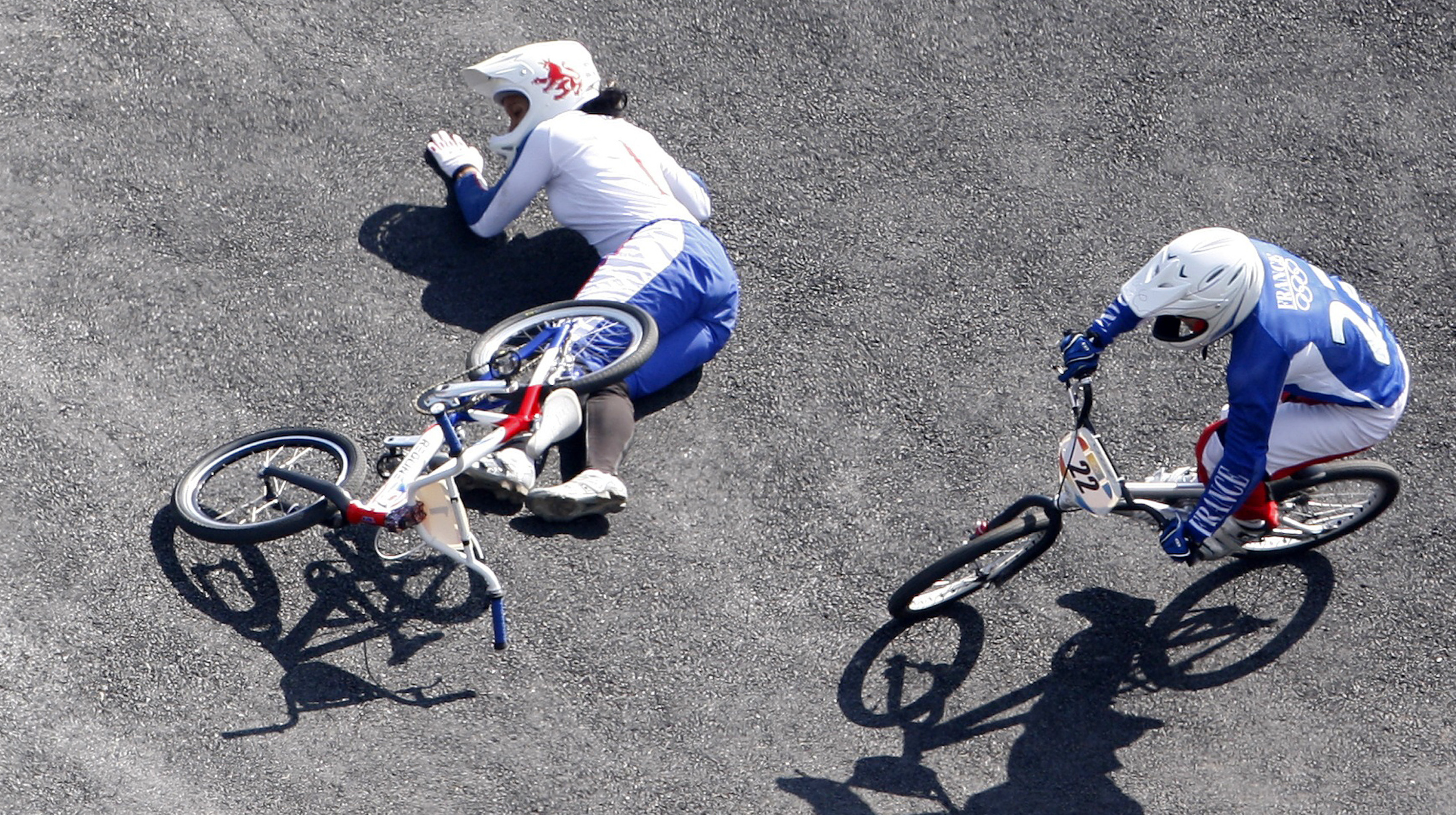 Laetitia le Corguille of France overtakes Shanaze Reade of Britain after Reade falls during the women's final run for the BMX cycling competition at the Beijing 2008 Olympic Games