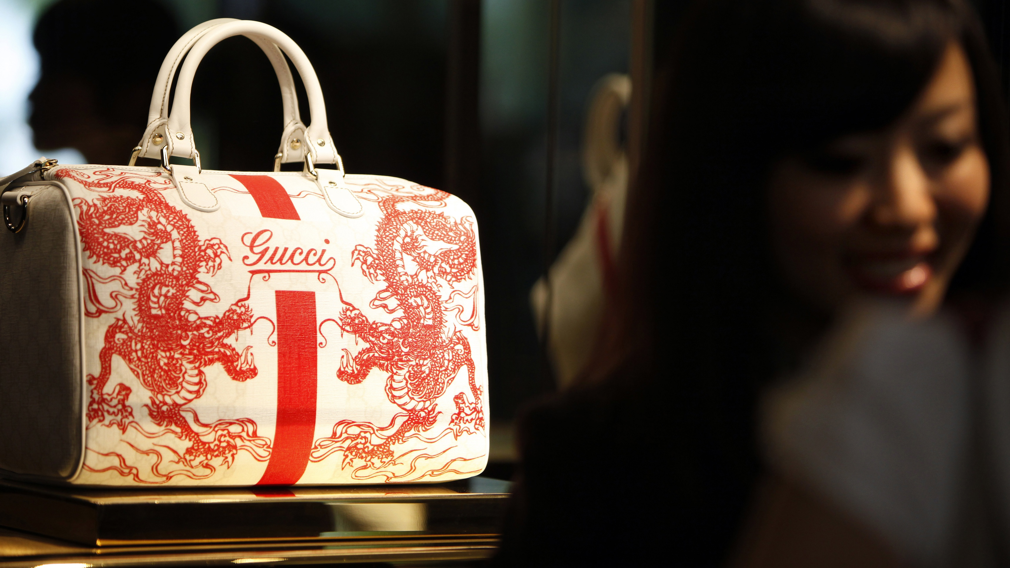 A staff member of the new Gucci flagship store in Shanghai chats with customers next to a bag on display on its opening day June 6, 2009. Luxury brand Gucci plans to open two to four more stores this year in China, after opening its 28th on Saturday, undeterred by uncertainty in the global economy as China is set to lead future luxury consumption, Gucci CEO Patrizio Di Marco said.