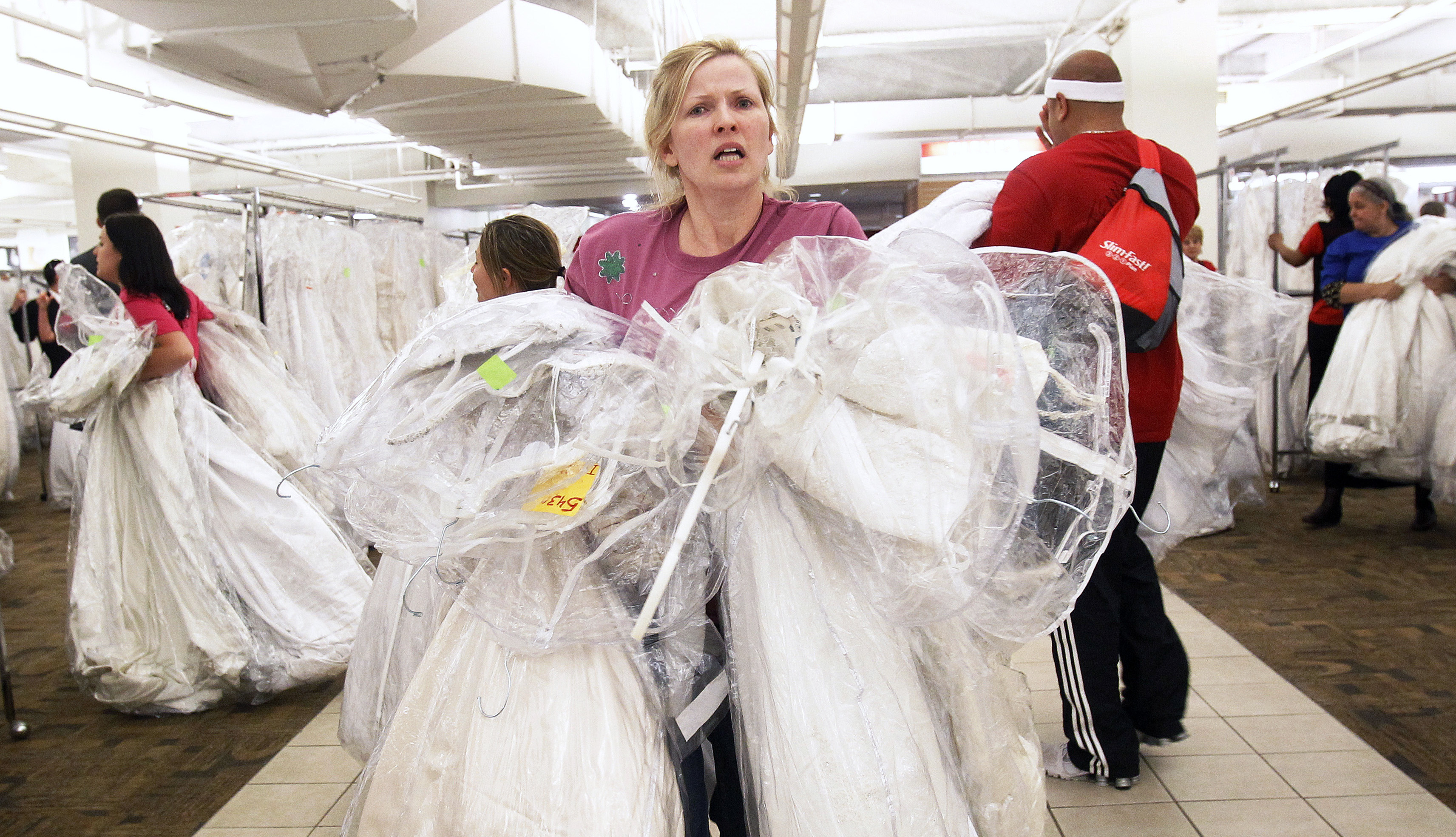 "A shopper carries bridal dresses during the Filene's Basement  ""Running of the Brides"" bridal dress sale in New York"