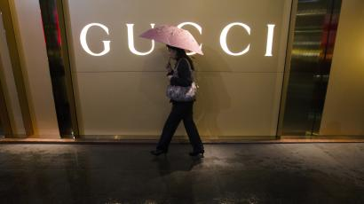 DATE IMPORTED:February 27, 2014A woman holding an umbrella walks past a company logo of a Gucci boutique outside a shopping mall amid rainfall in central Guangzhou, Guangdong province February 25, 2014. The world's biggest luxury brands are slowing their expansion in China as more consumers shop abroad, leaving mall operators holding the bag.