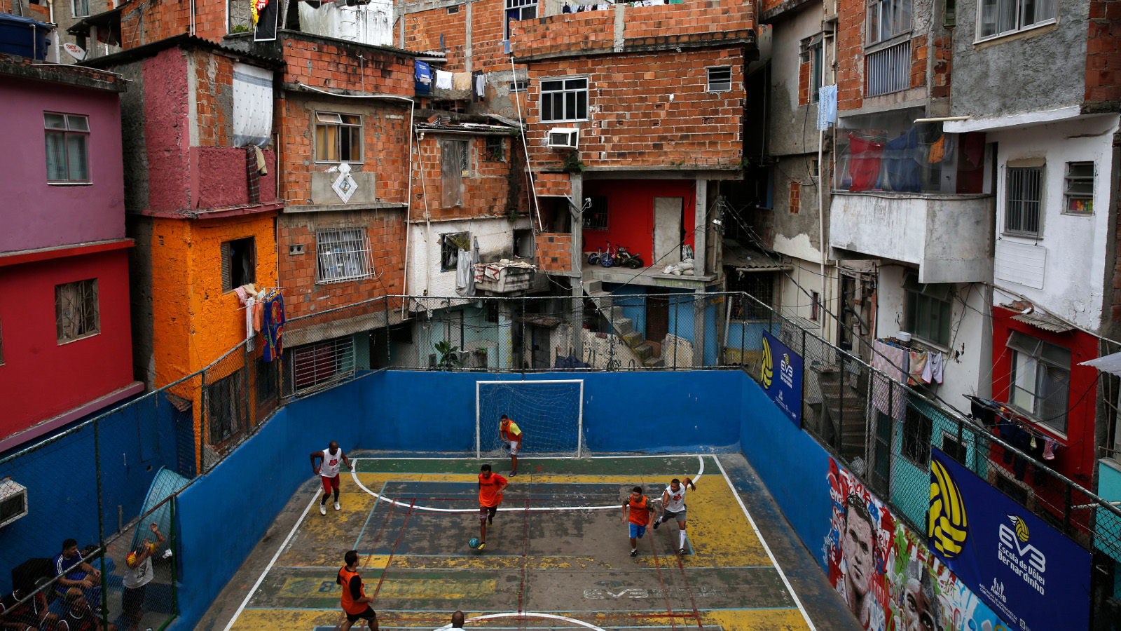 People take part in a soccer match held at the Tavares Bastos slum in Rio de Janeiro May 18, 2014. The World Cup will be held in 12 cities in Brazil from June 12 till July 13. REUTERS/Pilar Olivares (BRAZIL - Tags: SPORT SOCCER TPX IMAGES OF THE DAY)  FOR BEST QUALITY IMAGE ALSO SEE: GF10000109702