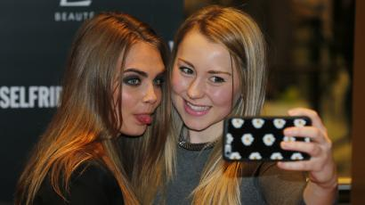 Model Cara Delevingne (L) poses for a selfie with a fan during a photo call at Selfridges department store in London.