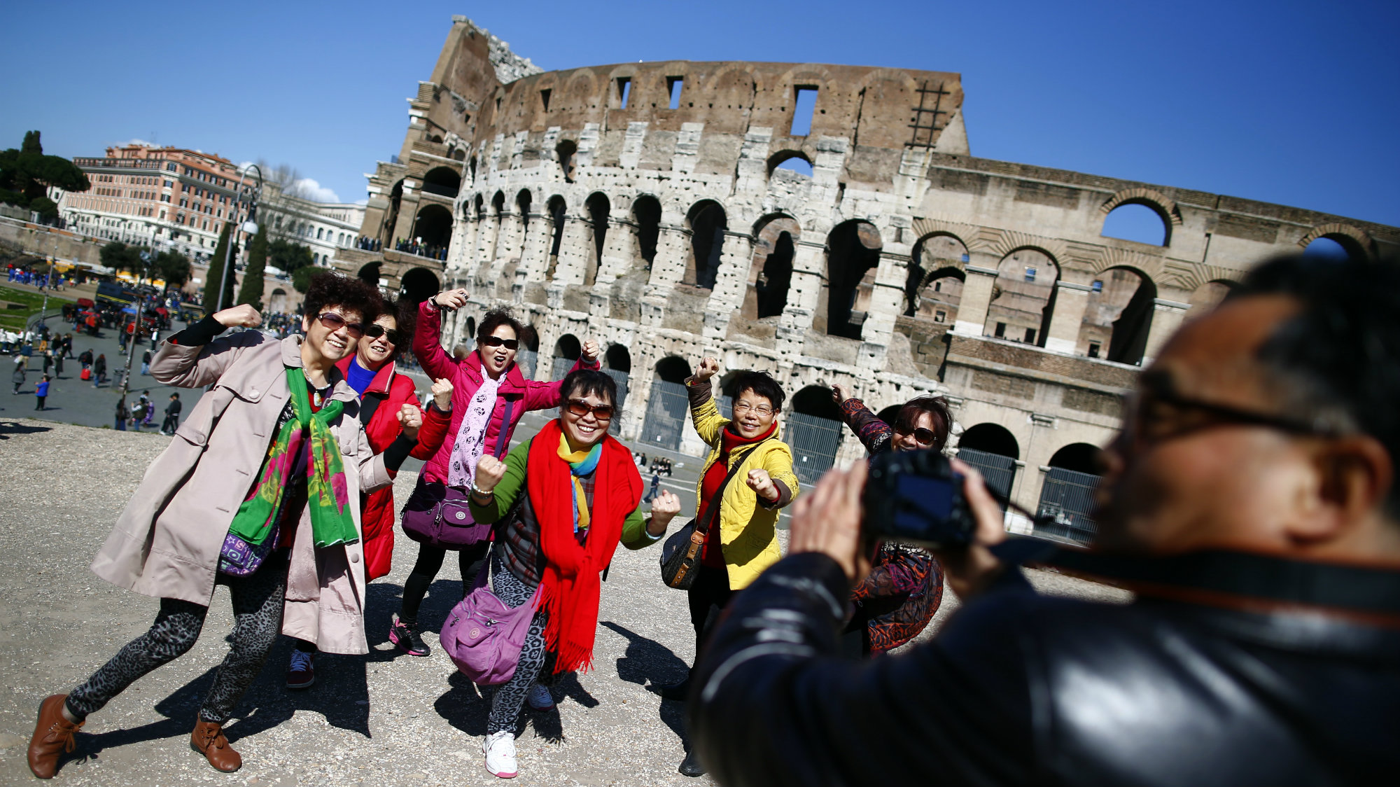 Tourists pose in front of the Colosseum in Rome.