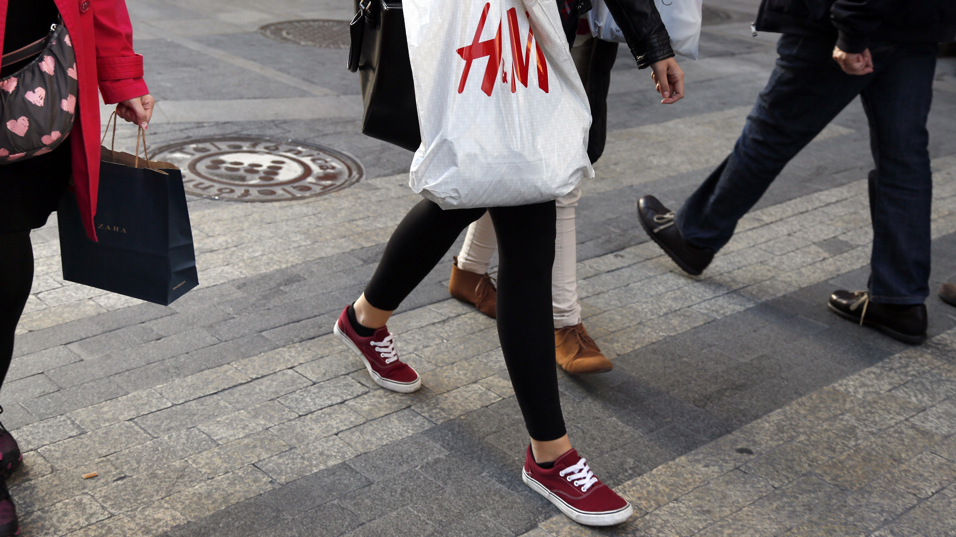 Women with Zara (L) and H&M (C) shopping bags walk at a shopping district