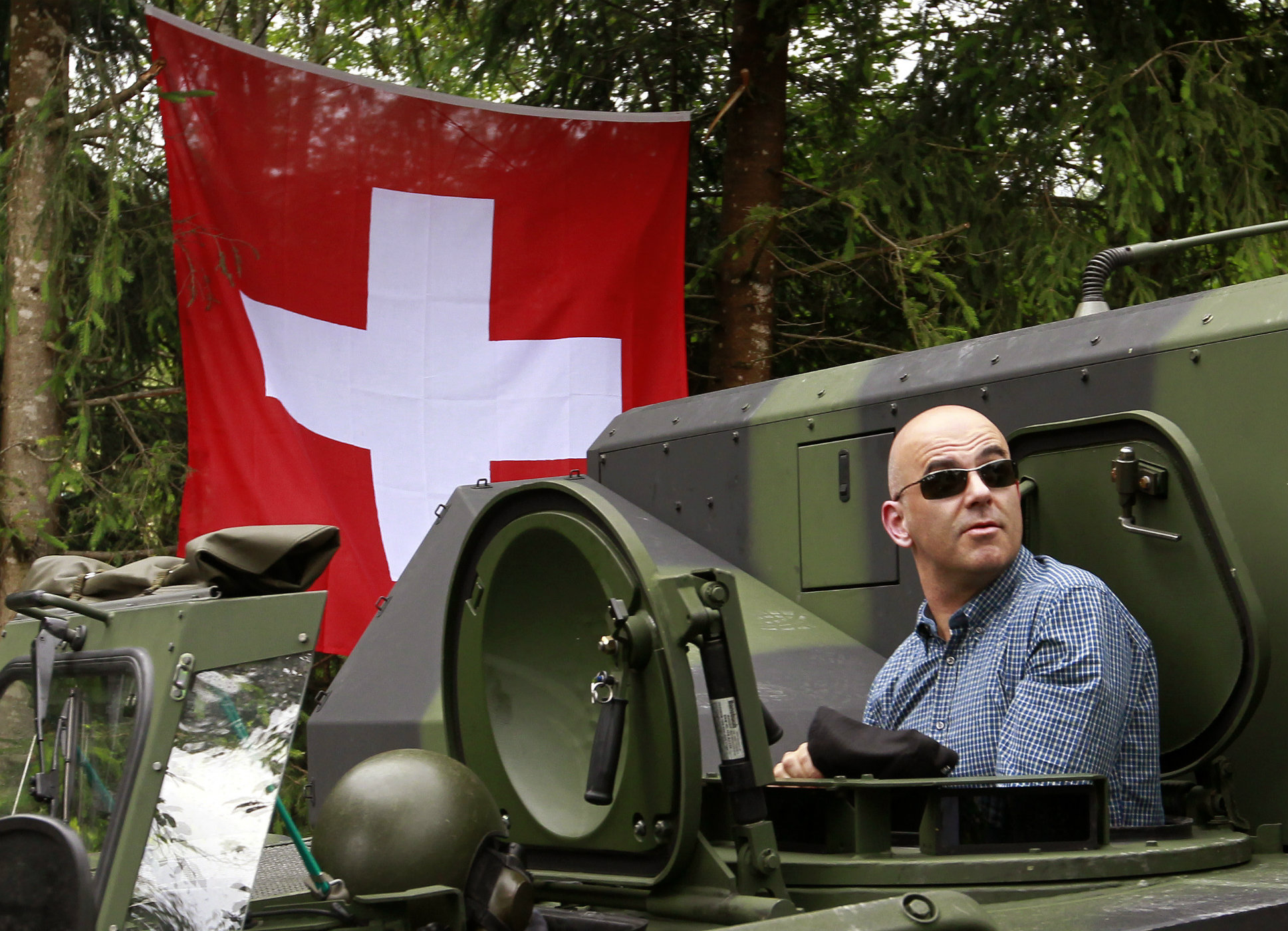 Swiss Interior Minister Alain Berset sits in a Swiss army tank in the village of Girenbad July 4, 2013. The members of the Swiss Federal Council are on a two-day visit in the canton of Zurich. REUTERS/Arnd Wiegmann