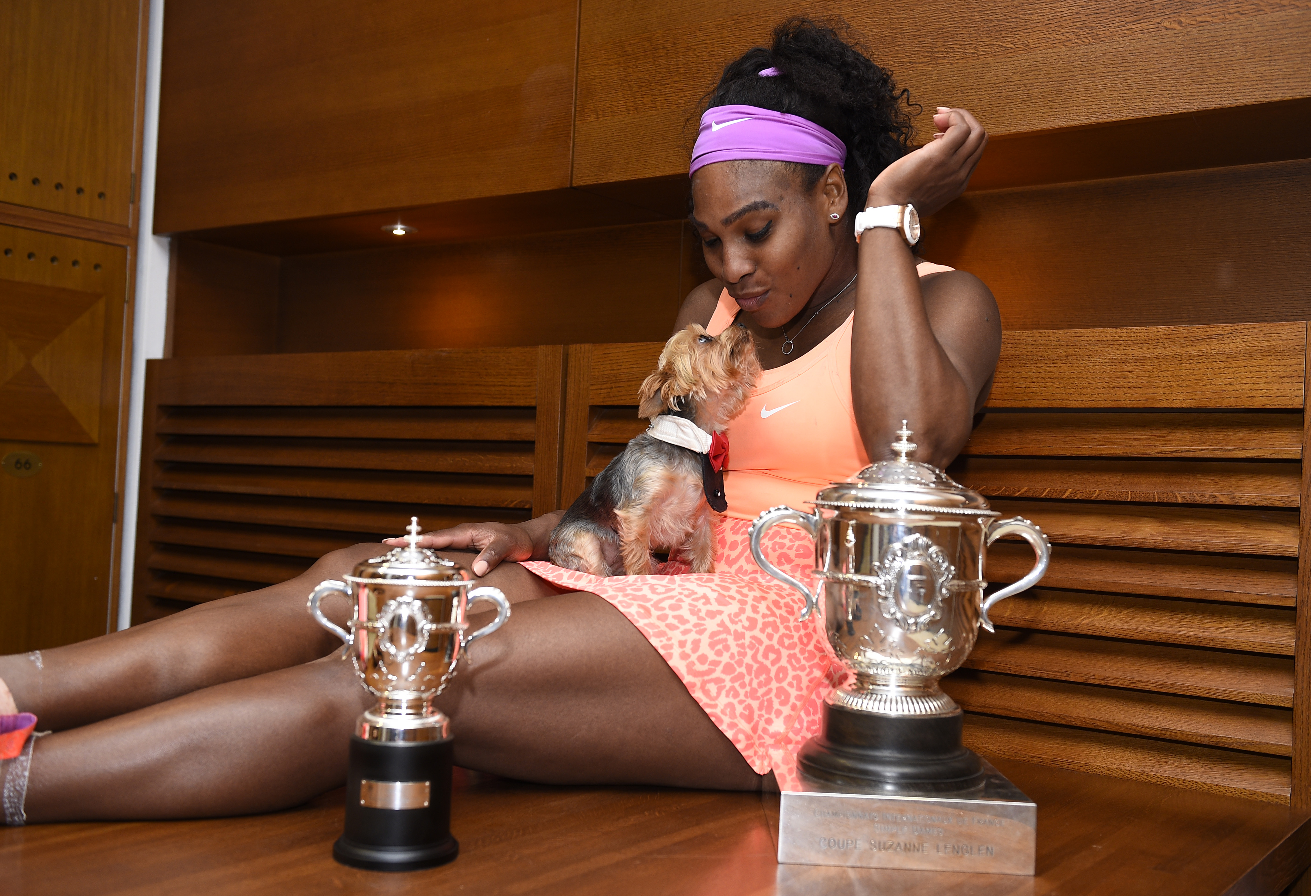 Serena Williams of the U.S. poses with her trophy and her dog named Chip in the dressing room after winning the women's singles final match against Lucie Safarova of the Czech Republic during the French Open tennis tournament at the Roland Garros stadium in Paris, France, June 6, 2015.