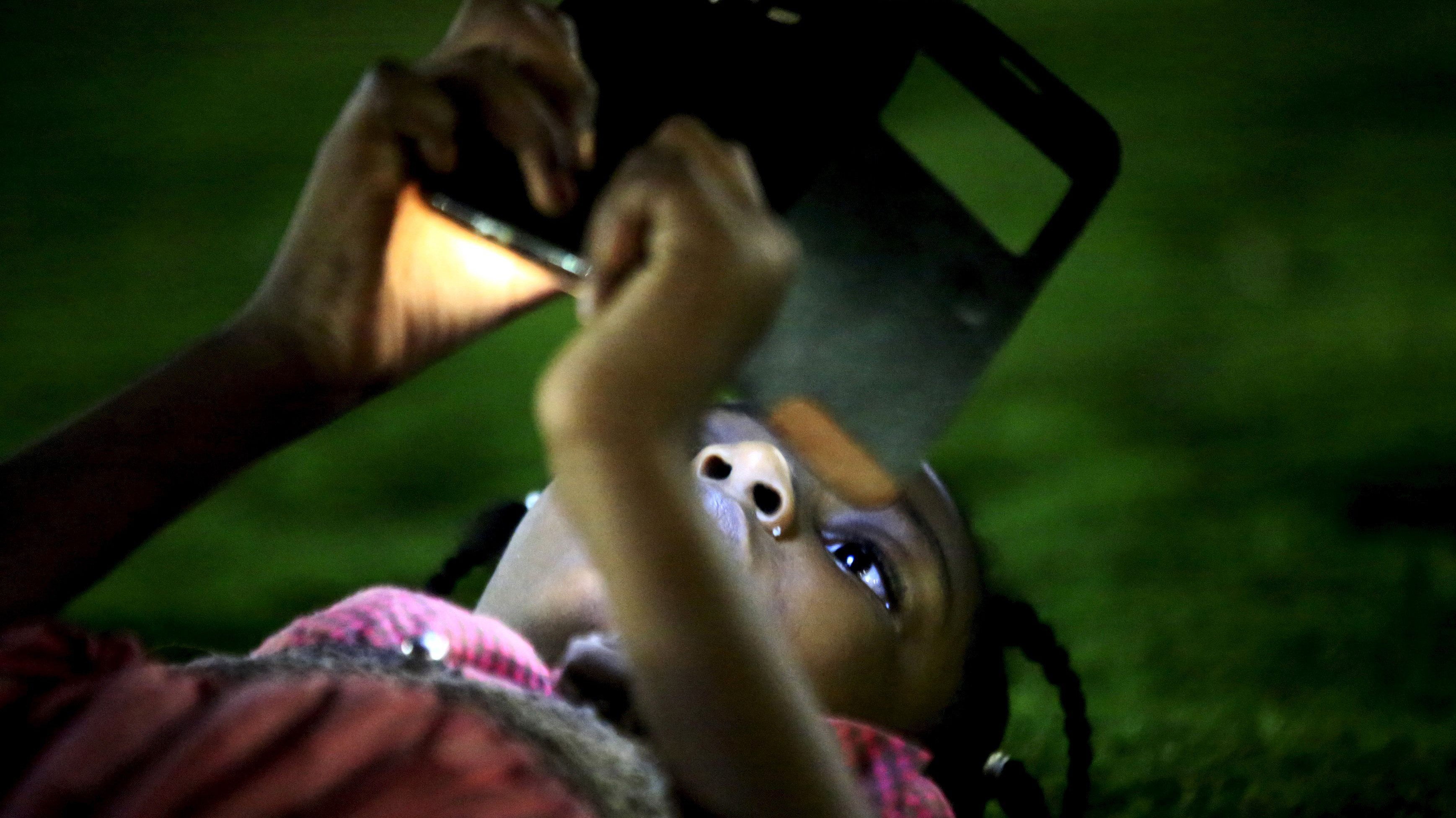 A girl uses her mobile phone during the evening at the National Park in Khartoum, Sudan, April 24, 2015.