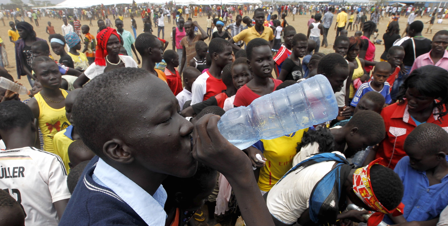 A refugee from South Sudan drinks water at a well during celebrations to mark World Refugee Day at the Kakuma refugee camp in Turkana District, northwest of Kenya's capital Nairobi, June 20, 2015. June 20 is World Refugee Day, an occasion that draws attention to those who have been displaced around the globe. REUTERS/Thomas Mukoya - RTX1HE60