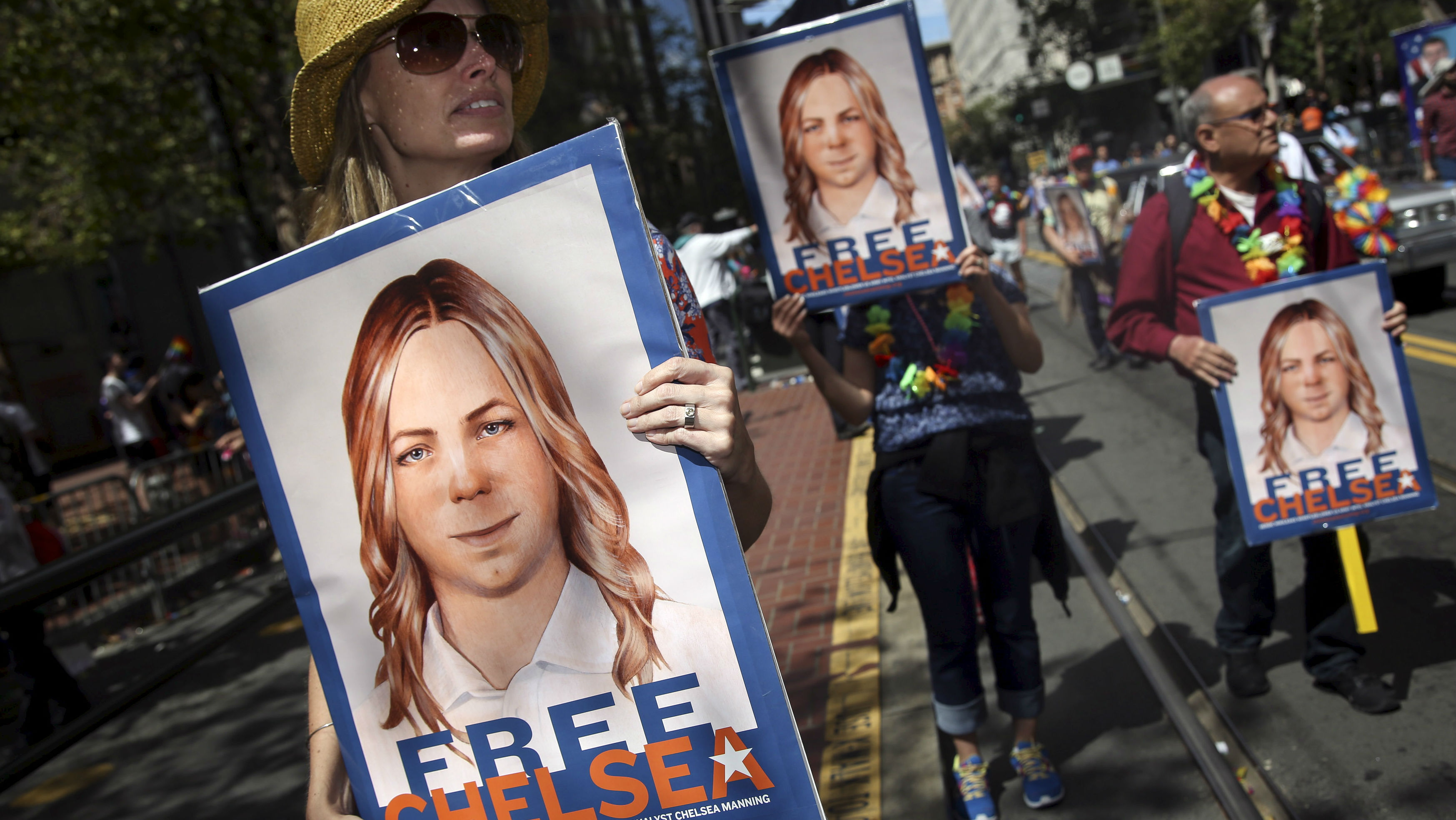 People hold signs calling for the release of imprisoned wikileaks whistleblower Chelsea Manning while marching in a gay pride parade in San Francisco, California June 28, 2015. REUTERS/Elijah Nouvelage