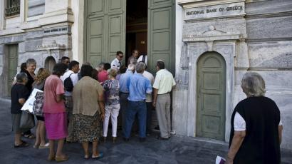 People wait to enter a National Bank branch in Athens.